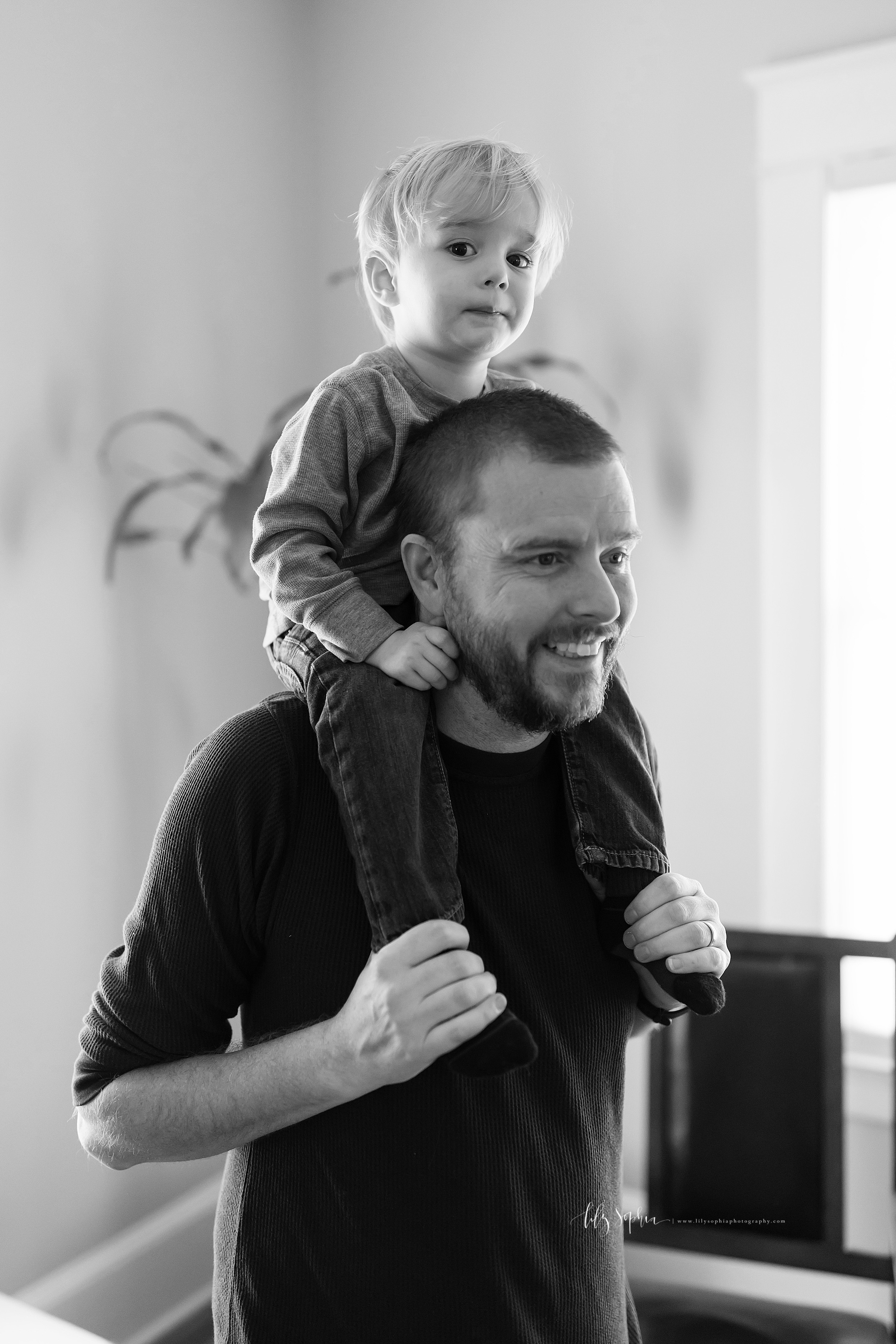Black and white lifestyle photo of a toddler riding on the shoulders of his dad in his home in Atlanta in natural light.