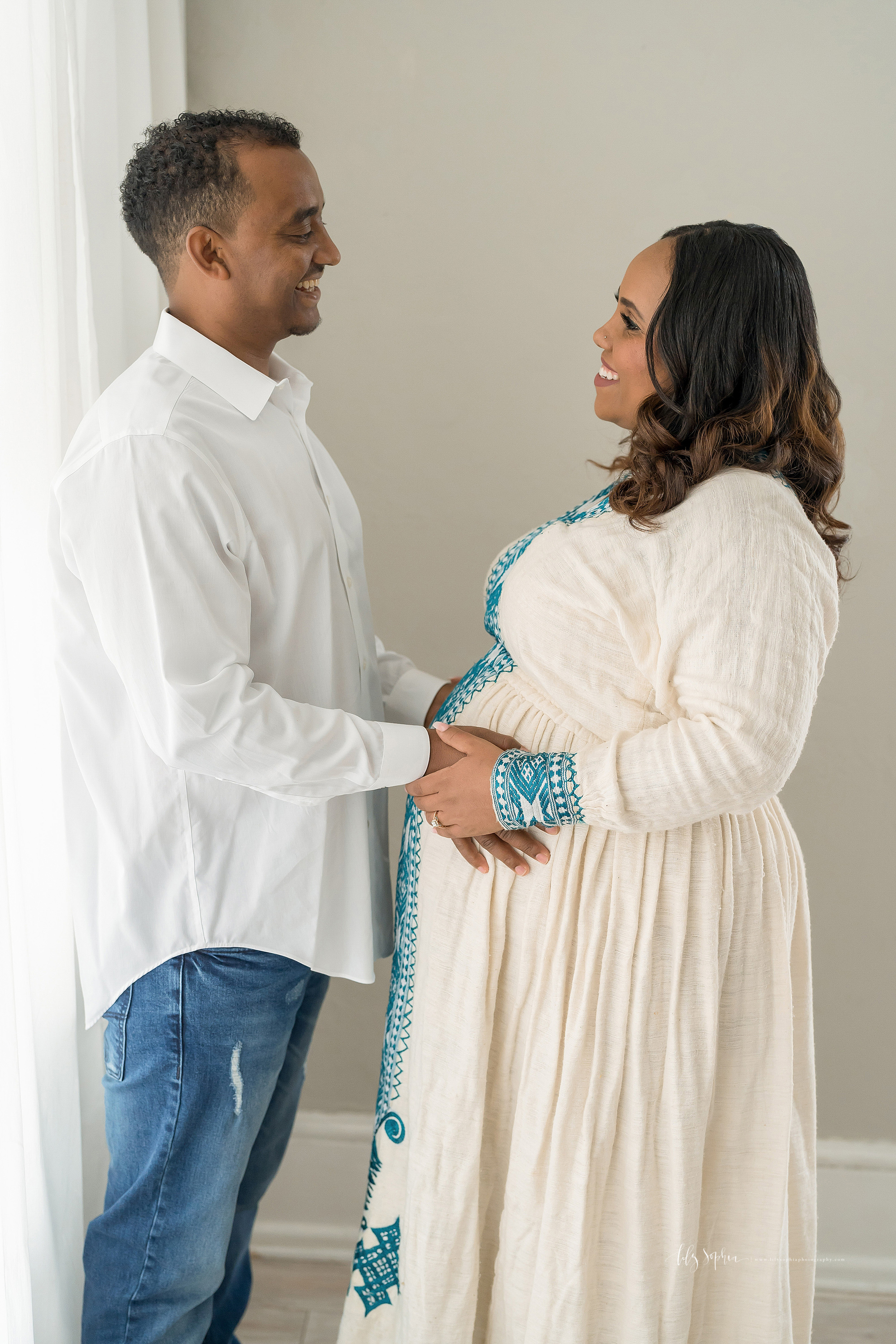 Maternity photo of a happy Ethiopian couple taken by Lily Sophia Photography in a natural light studio in Atlanta.  Dad is facing his wife.  The two of them are smiling at one another.  Dad has his hands at the waist of his wife and his wife has her hands over top of his.  Mom is dressed in a traditional Ethiopian dress.  Dad is dressed in a long sleeve wife button down shirt and blue jeans.