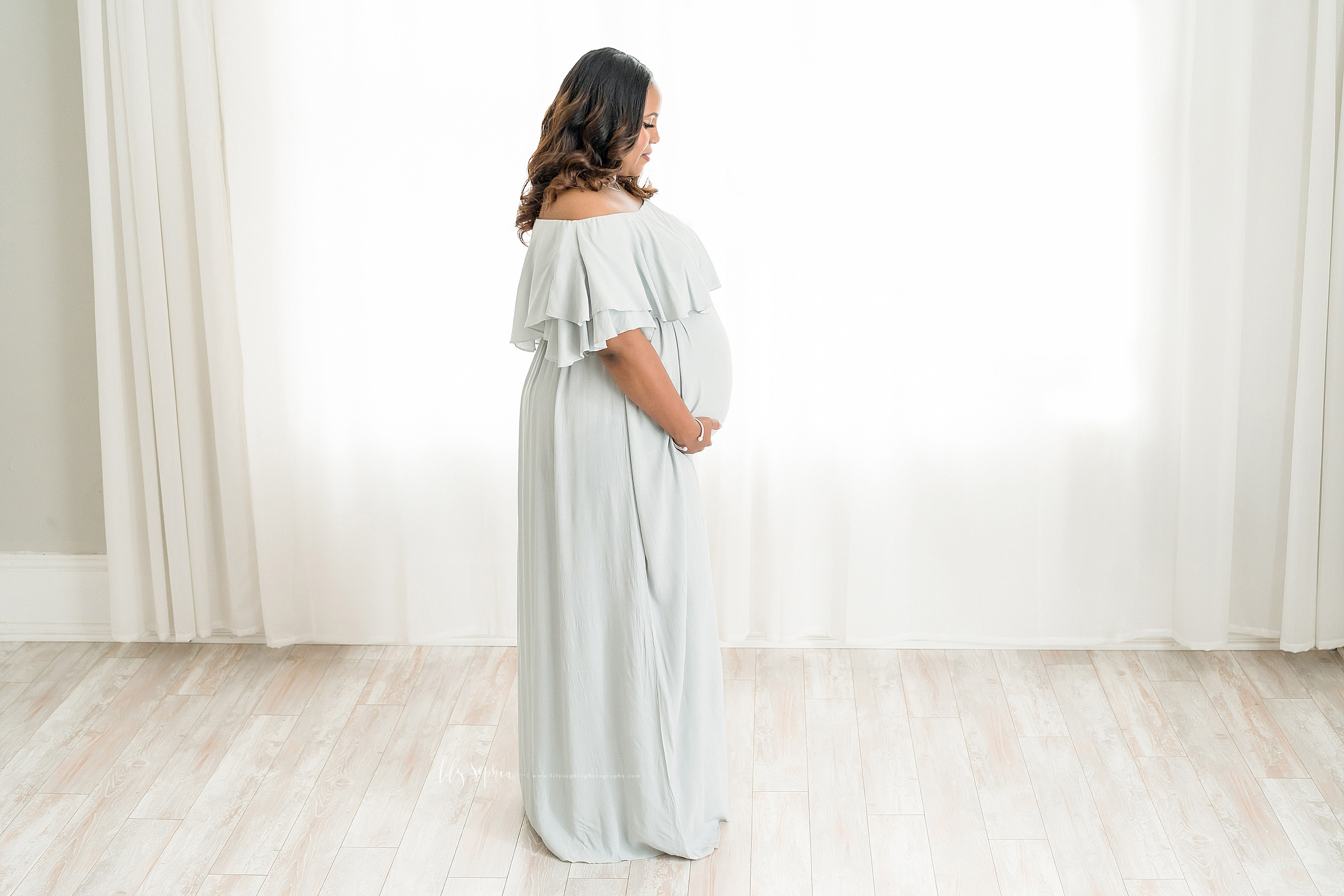 Maternity photo of an African American woman standing in front of a window in a natural light studio in Atlanta.  She is wearing a pale grey knit maternity dress that is off her shoulders.  It has a two-tiered large ruffle at the neckline.  Mom is holding the bottom of her belly to show off her womb.
