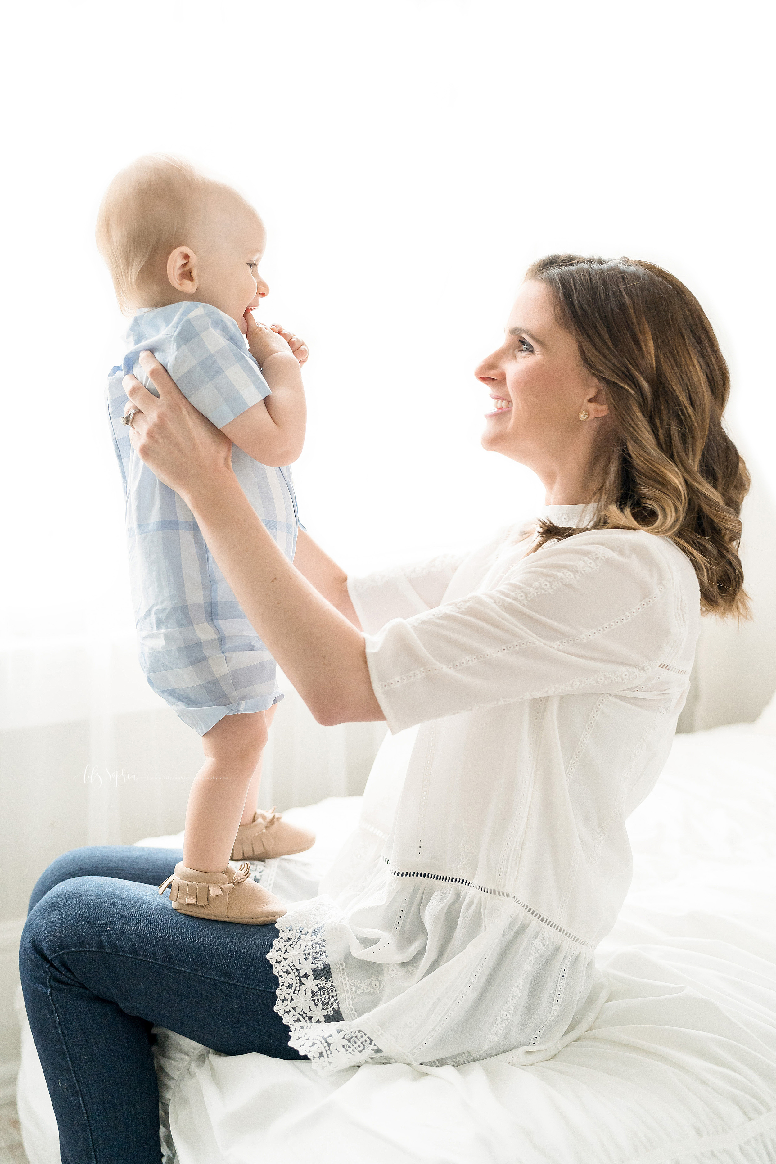 Photo of a mother and her one year old son in Lily Sophia Photography Studio in Atlanta. The mom is sitting on a bed in front of a window. She is wearing a white linen elbow length sleeved  shirt with lace along the bottom edge and blue jeans. Her son is wearing a blue and white plaid short sleeve romper and tan leather fringed moccasins. Mom is holding her son under his arms while he stands on her mother's lap. The baby boy has his hands in front of his chest and his right thumb in his mouth. The brunette mom is looking at her son and smiling at him.