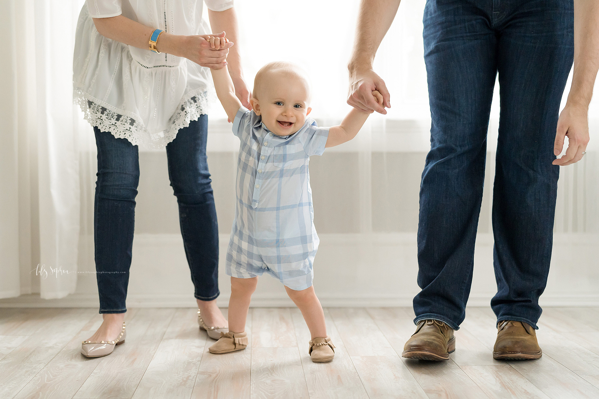 Photo of Mom and Dad helping their smiling one year old walk in an Atlanta studio.  Mom is holding the one year old's right hand and Dad is holding the one year old's left hand as they help him take his first steps.