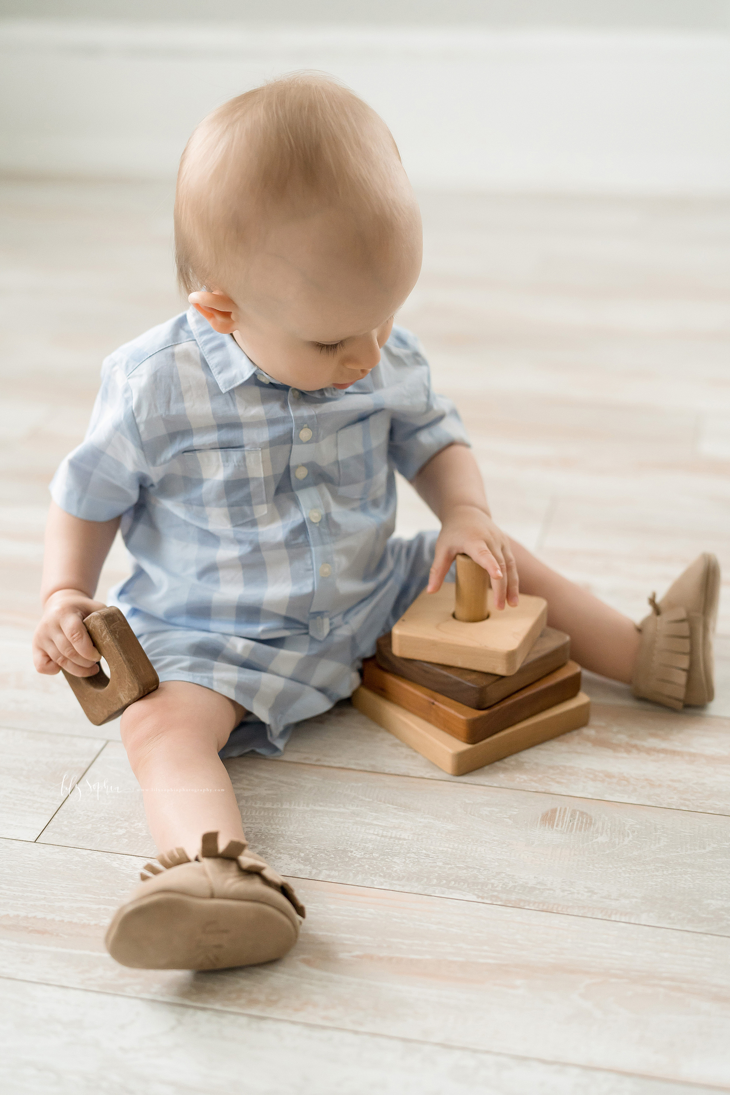 Photo of a one year old little boy playing with a wooden toy taken by Lily Sophia Photography in a natural light studio in Atlanta. The little boy is wearing a blue and white plaid shirt and shorts. He is sitting on the wooden floor with his legs spread apart and tan leather moccasins on his feet. The wooden stacking toy is between his legs. He has one of the stacking pieces in his right hand and he is holding the stacking tower on the floor with his left hand.
