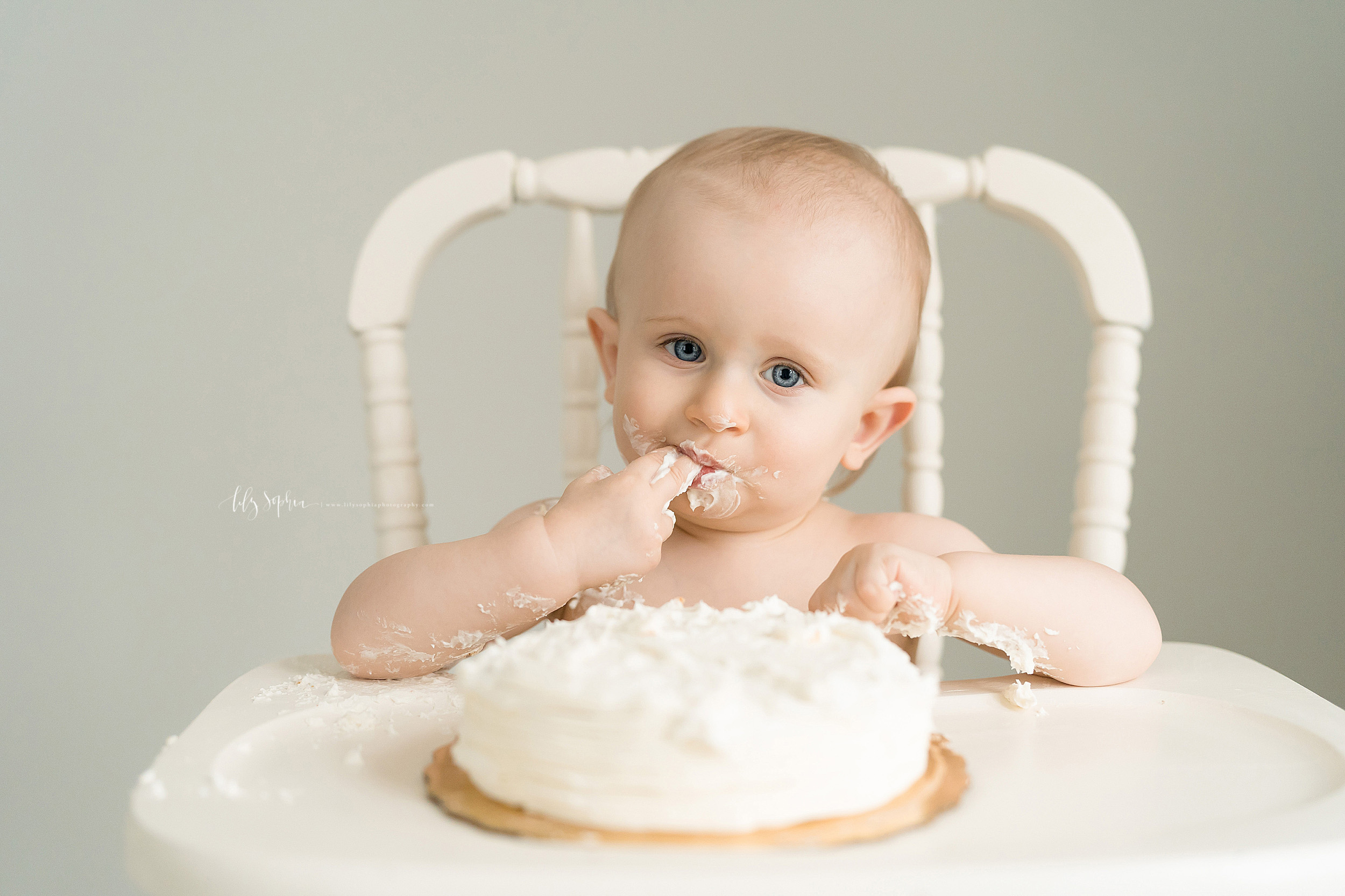Photo of  a one year old blue eyed boy eating his smash cake in an Atlanta studio.  The one year old is sitting in an antique cream colored wooden high chair.  He has his right pointer and middle finger in his mouth licking off the icing.  The cake is sitting in front of him on the tray of the high chair.  His left arm is resting on the tray of the high chair and he has icing on both forearms.