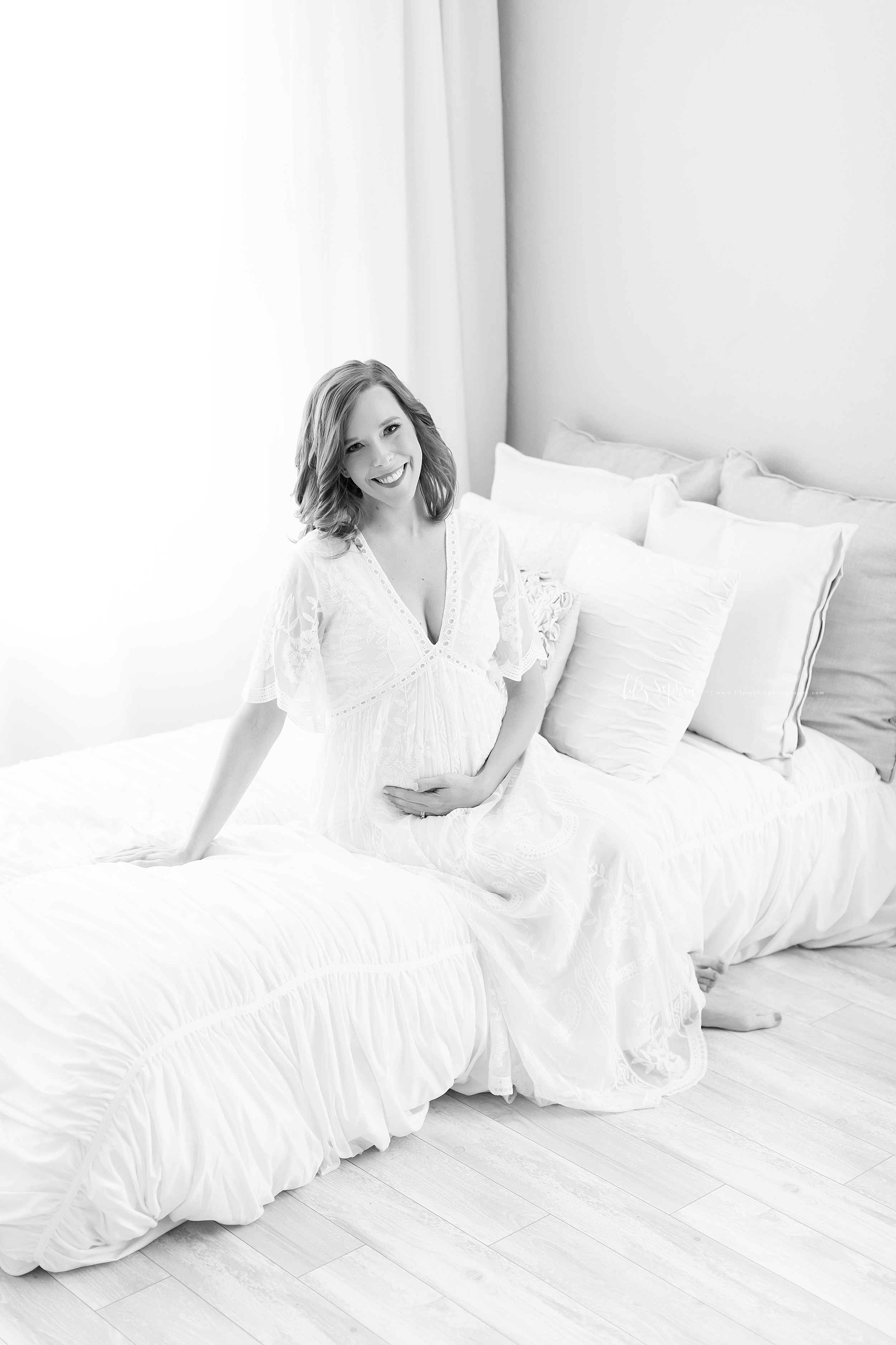 Maternity photo in black and white taken in the Lily Sophia Photography Studio in Atlanta.  The brunette mother sits on a bed as she wears a V neck white lace gown with bell sleeves.