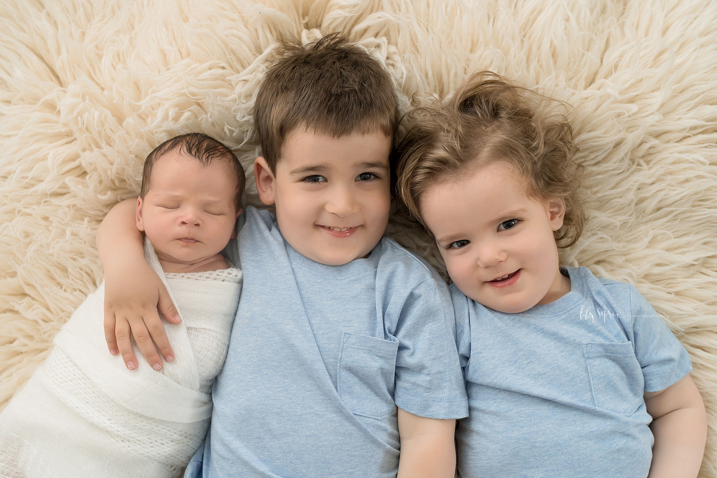 Photo of a newborn with his older brothers. The three brothers are laying on their backs on a tan fur blanket. The infant is wrapped to his chin in a soft white swaddle blanket and is on the left side of the photo. His brown haired, brown-eyed brother has his hand around his shoulder as he smiles and is in the middle of the photo. The younger blond haired brother is on the right of the photo  The older brothers are wearing light blue T-shirts with single pocket on the left hand side of the shirt.