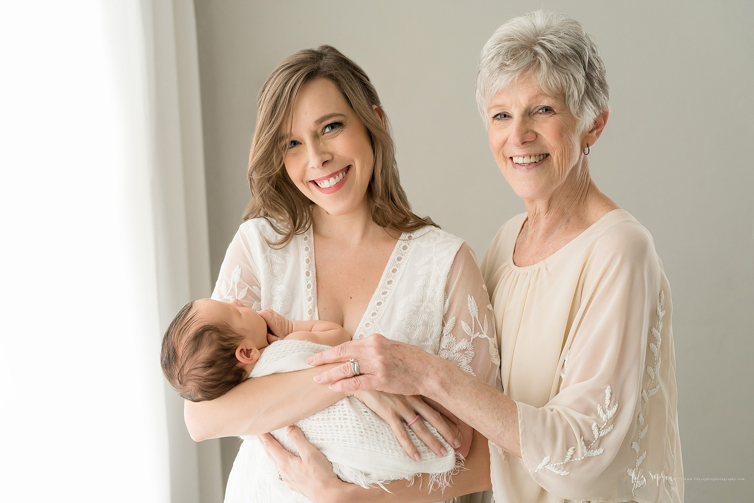 Photo of Grandma, mother and grandson in a natural light studio in Atlanta. Brunette mom is standing while holding her newborn son wrapped in a swaddle blanket in her arms as Grandma stands next to her on her left hand side and places her left hand on Mom's right hand.  Mom is wearing a white V-necked gown with sheer bell sleeves.  Grandma is wearing a scoop necked taupe knit dress with three-quarter length sleeves.
