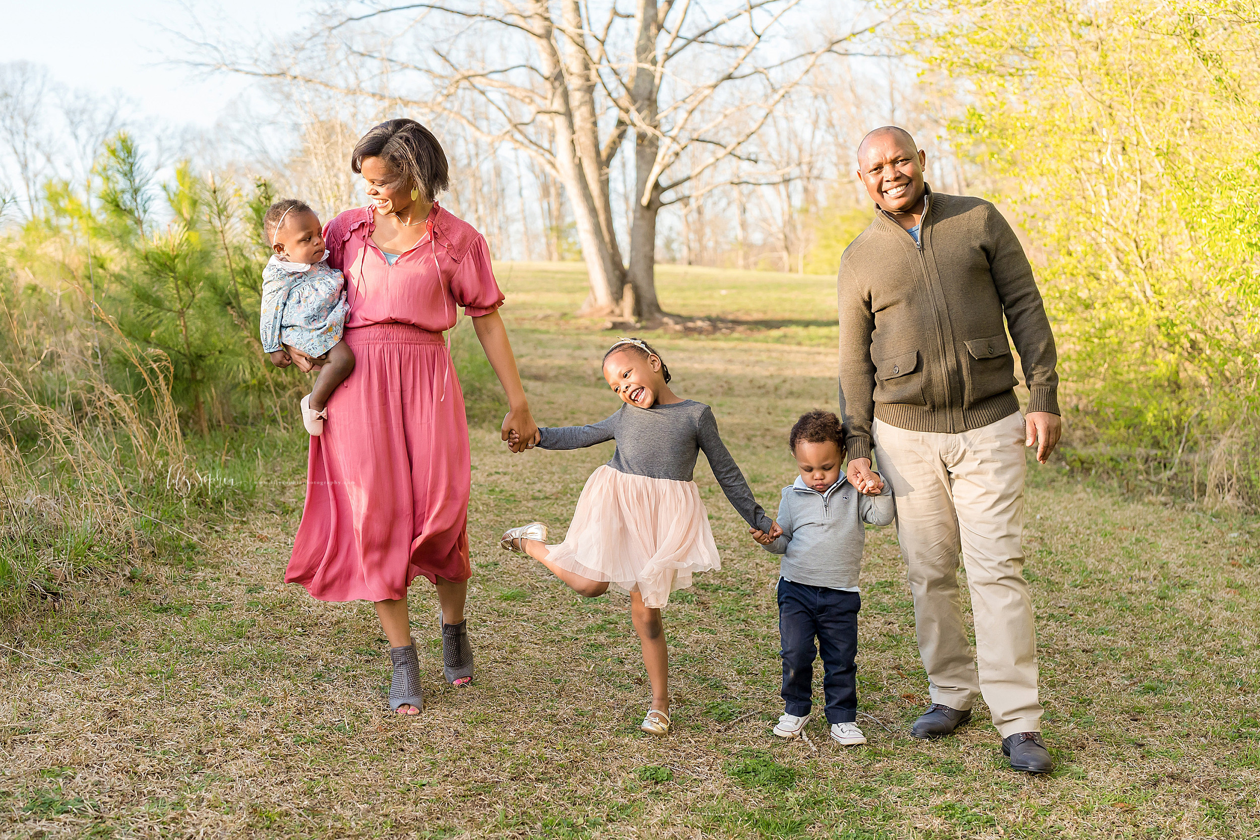 African-American family of five walk in an Atlanta field at sunset.  Mom is on the left holding her one year old daughter on her right hip.  Her other daughter is holding her mom's left hand and her toddler brother's hand.  Dad is on the right holding the toddler's other hand.