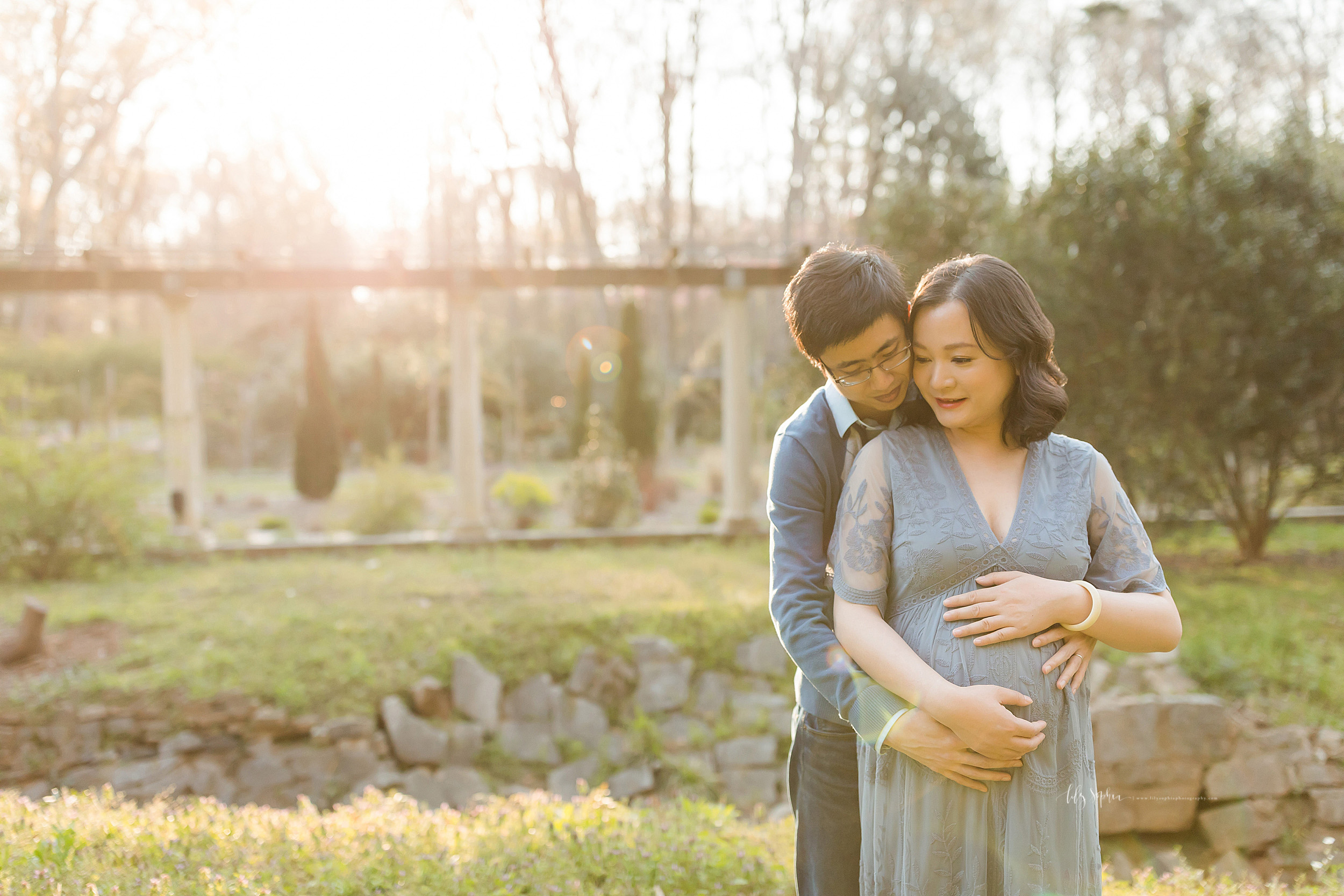 Pregnant Asian couple in at Atlanta garden for a photo shoot with Lily Sophia Photography at sunset. The husband is standing behind his wife with his right cheek against her left cheek. His wife is holding the top of her womb with her left hand. The husband is holding the bottom of her womb with his right hand and his wife has her hand on top of her husband's.  The couple is deep in thought.