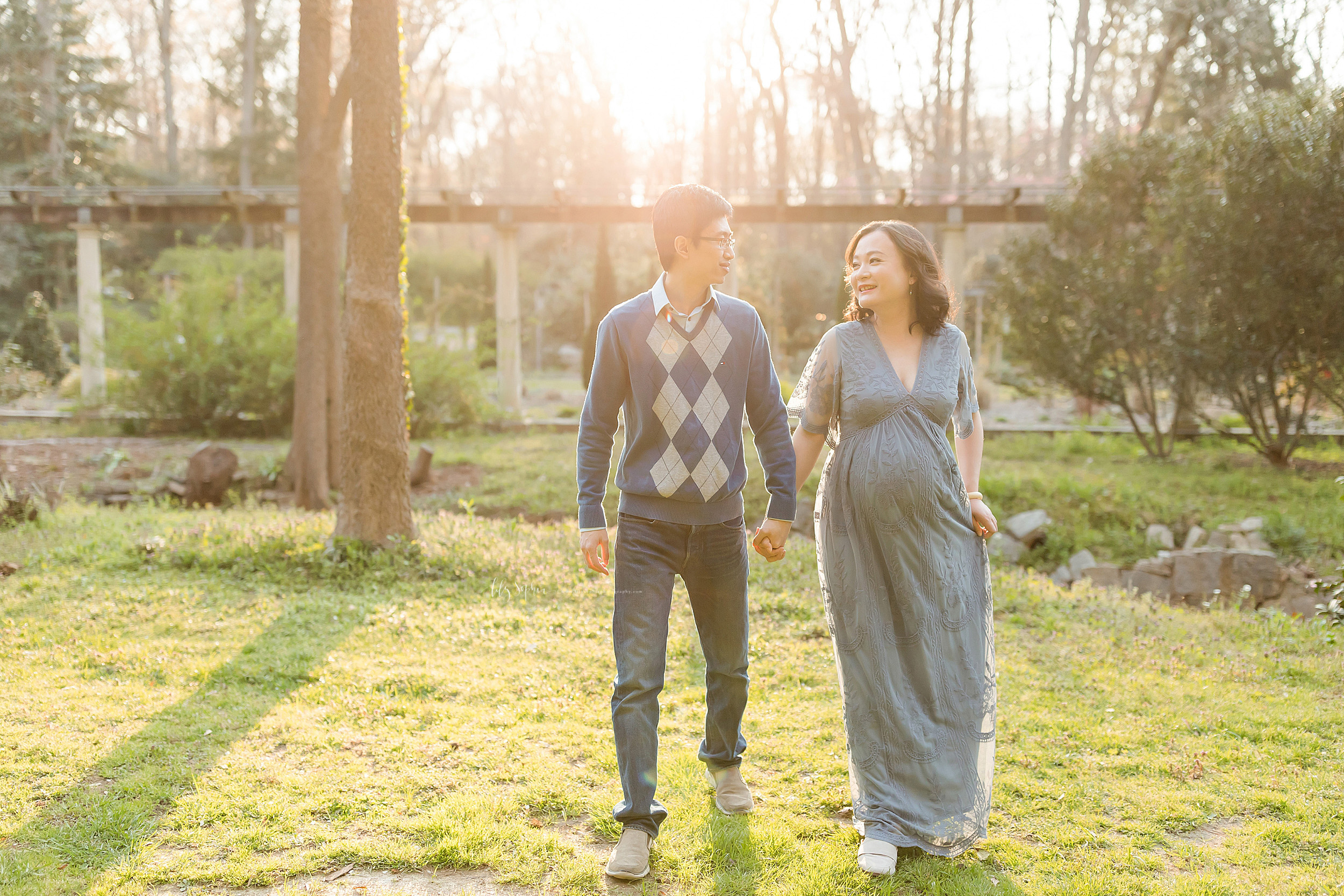 Maternity photo of an Asian couple walking in a garden at sunset in Atlanta. The husband is wearing a light blue shirt under a wedgewood blue pull over sweater with an argyle print on the front of the sweater and blue jeans. His wife is wearing a short sleeve V-necked wedgewood blue full-length gown. They are holding one another's hand as they look at each other and walk in the garden.  The wife holds her dress with her left hand as the sun sets in the background.