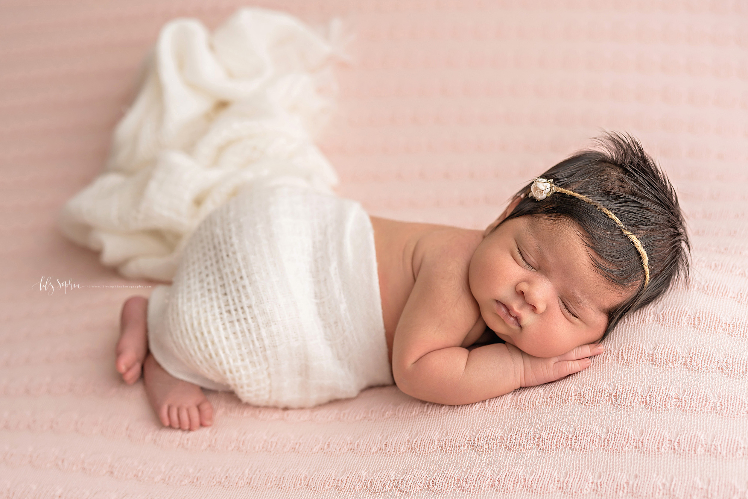 Photo of an infant Indian girl lying on a pink blanket with her feet sticking out of a soft white swaddle blanket that covers her bottom.  The infant girl is sleeping on her stomach with her hands under her face.  The infant girl has her face turned to the right and she has a headband with a single rose in her dark hair.  The photo is taken by Lily Sophia Photography.