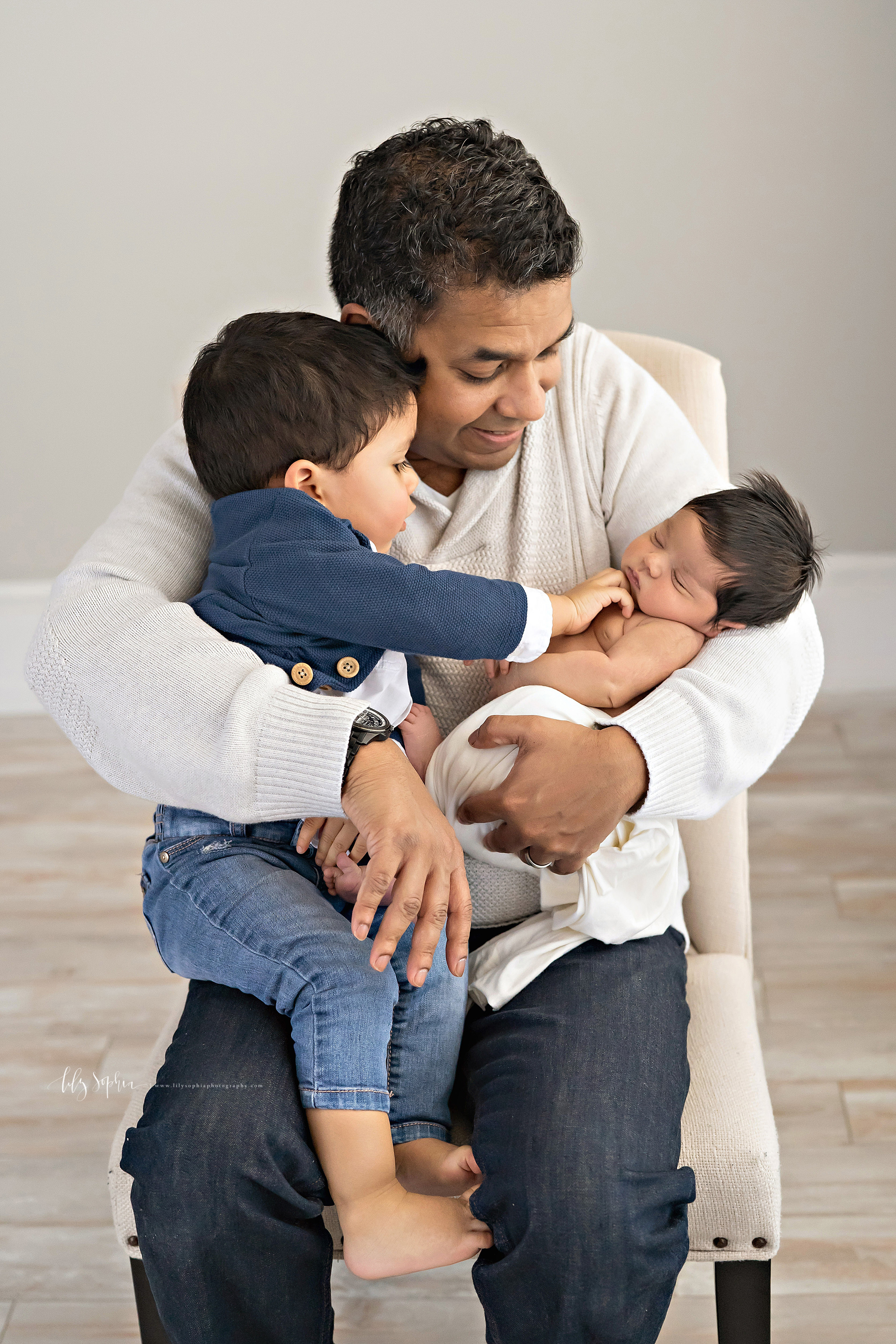 Photo of an Indian father sitting with his two young children in an Atlanta natural light studio.  The father is holding his toddler son on his right knee.  The toddler is tickling his infant sister under her chin as she sleeps in her father's left arm.