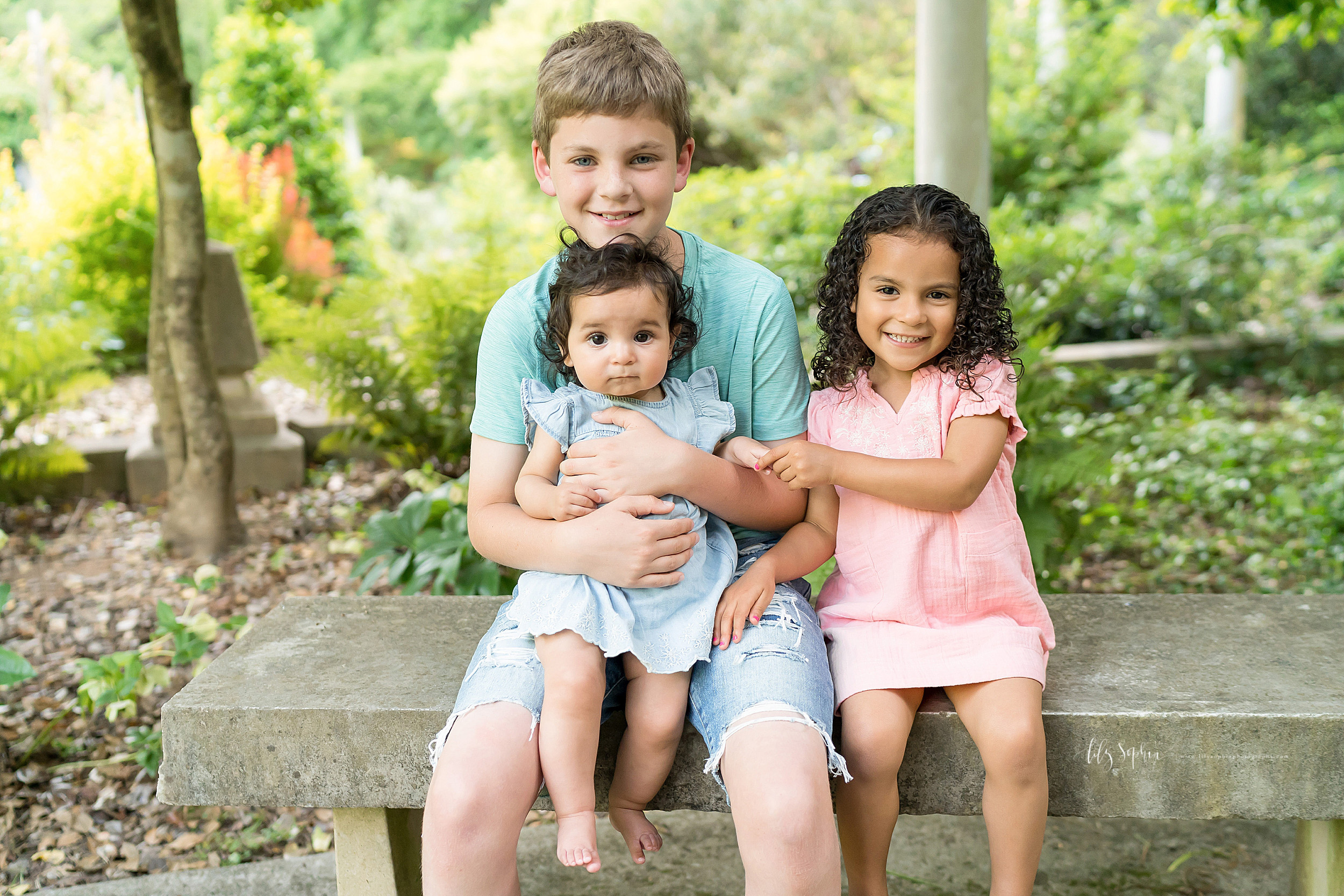 Photo of three happy siblings sitting in an Atlanta garden.  The brother and two sisters are sitting on a cement bench.  The older brother is holding his baby sister on his lap.  His younger sister is sitting next to him and is holding her baby sister's hand.