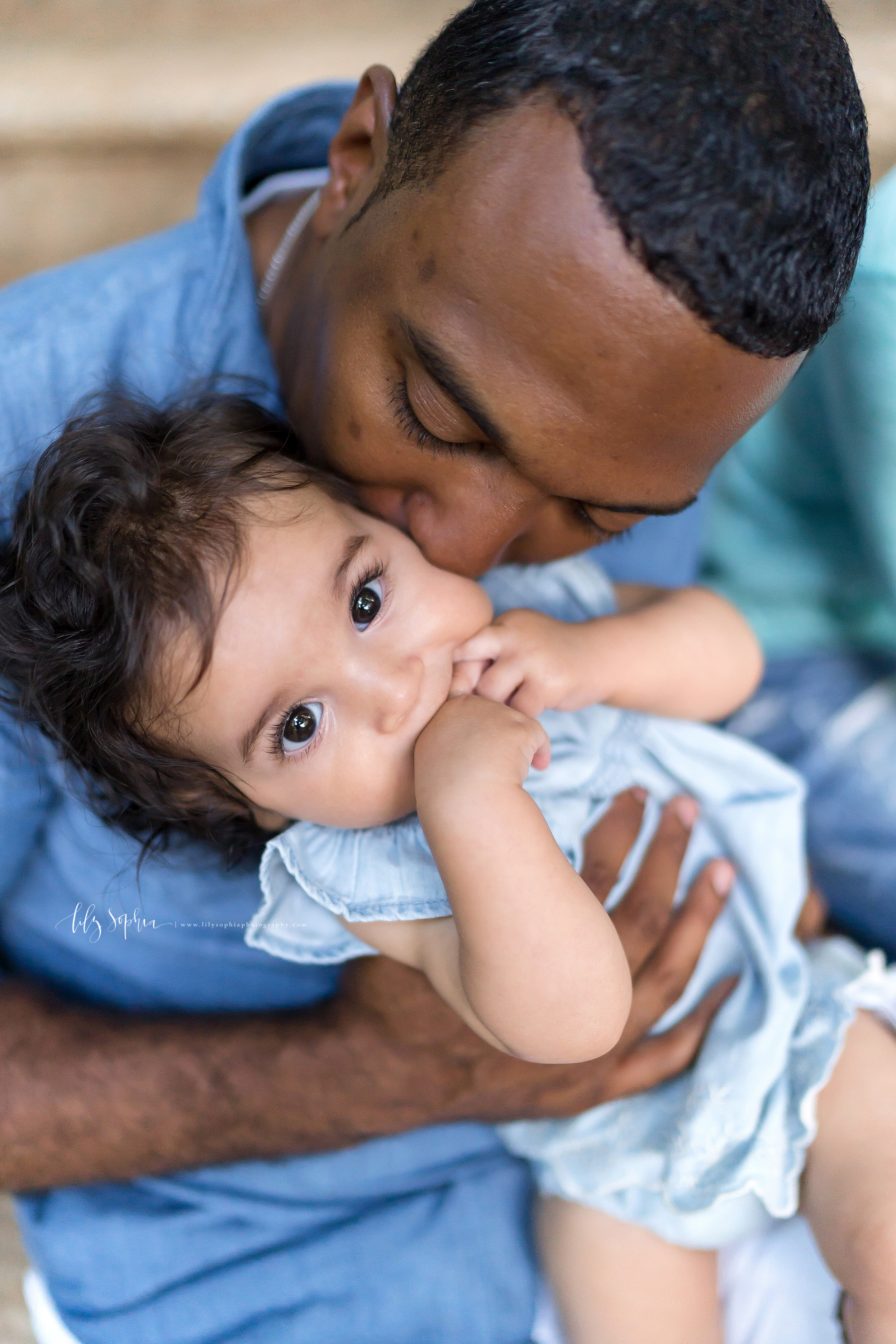 Photo of an African-American father with his baby girl in an Atlanta garden. The father is kissing the cheek of his daughter as he holds her while standing up.  The baby daughter has her fingers in her mouth.