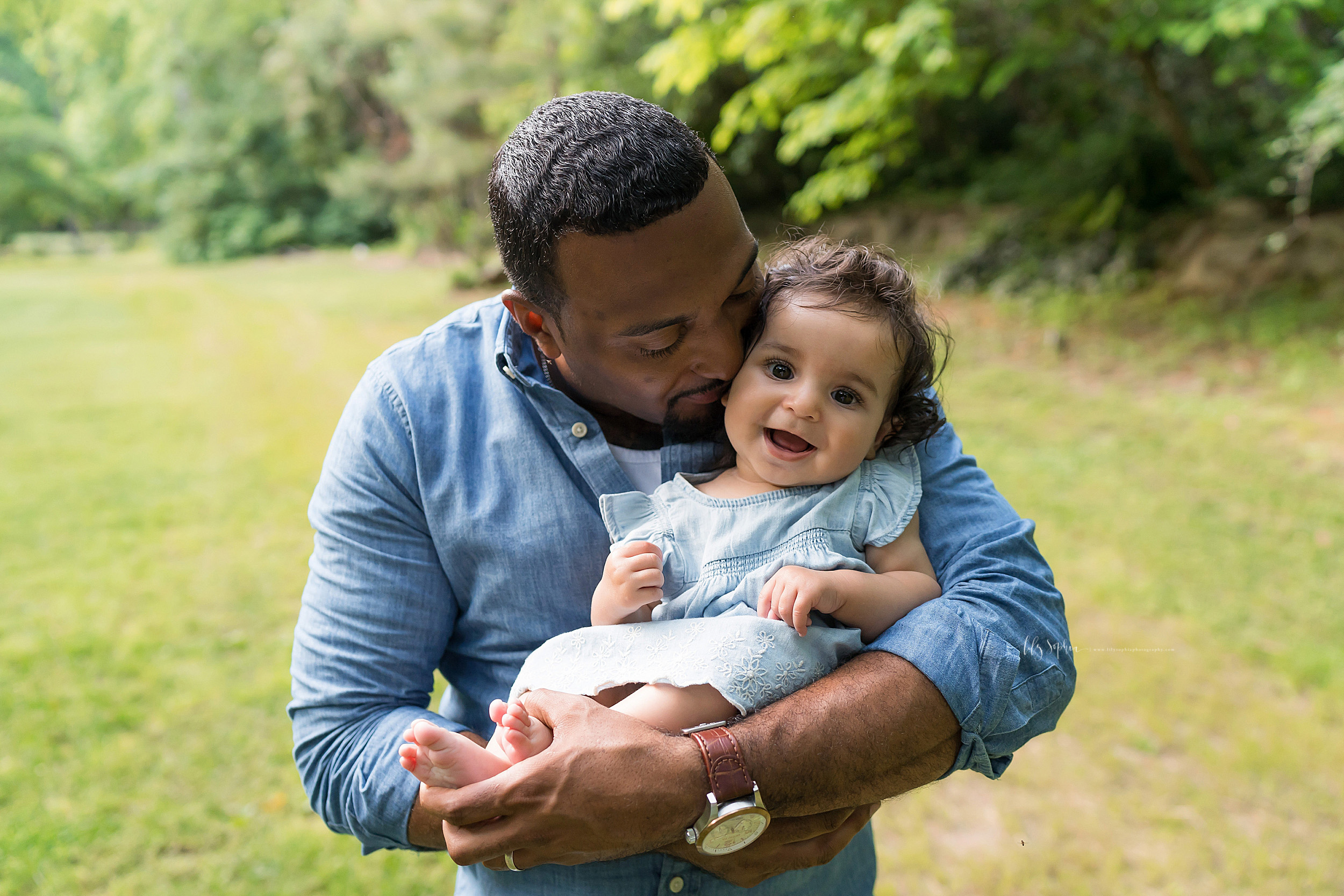 Photo of an African-American dad holding his precious baby girl taken by Lily Sophia Photography in an Atlanta garden.  Dad has his baby girl sitting in his arms as he holds her little feet.  He is whispering in her ear and the little girl is smiling.