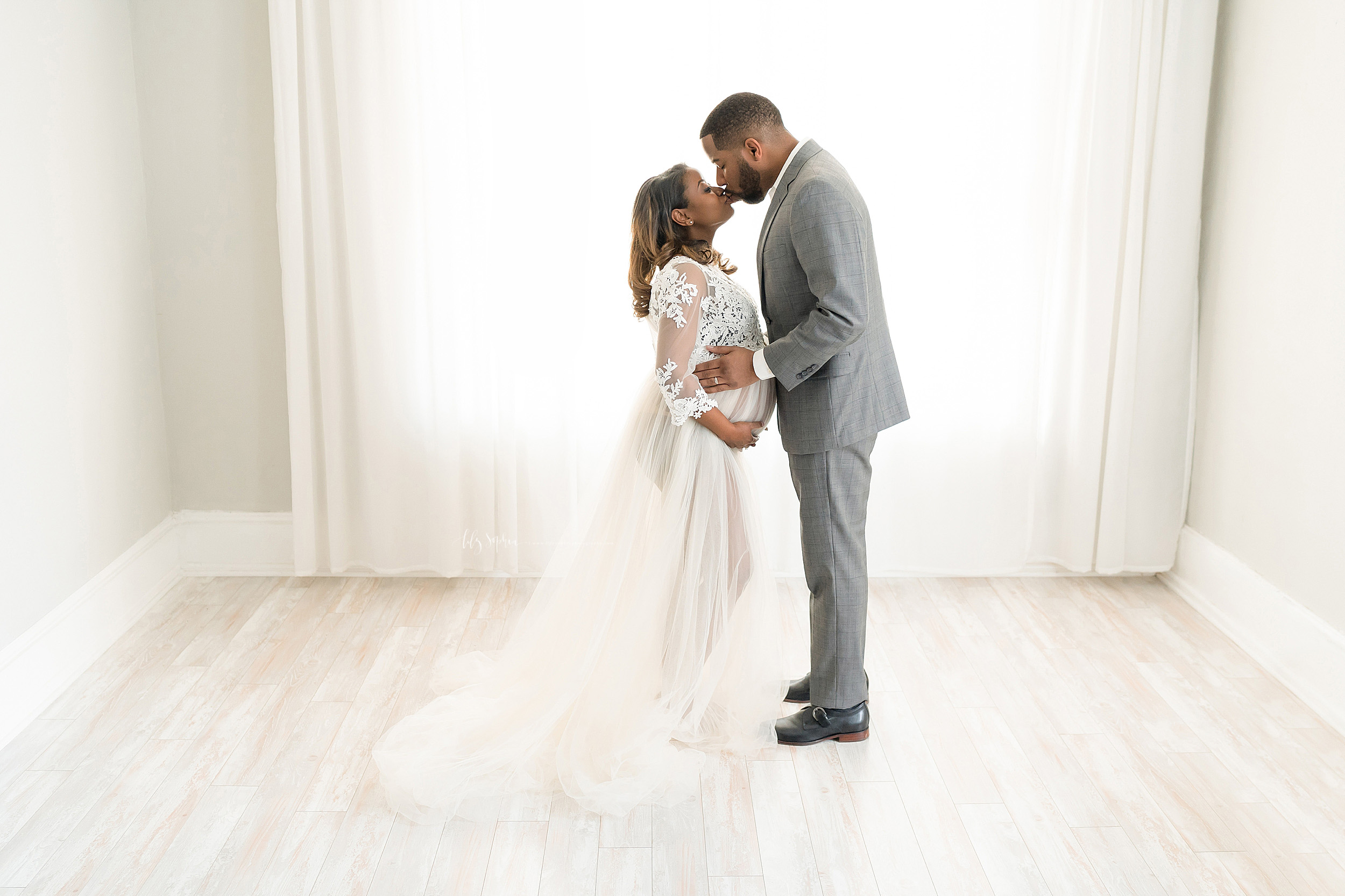 Maternity photo of an African-American couple taken by Lily Sophia Photography in a natural light studio in Atlanta.  The husband and wife are facing one another.  Mom is framing her belly with her hands as she kisses her husband who is holding her belly at her waist.