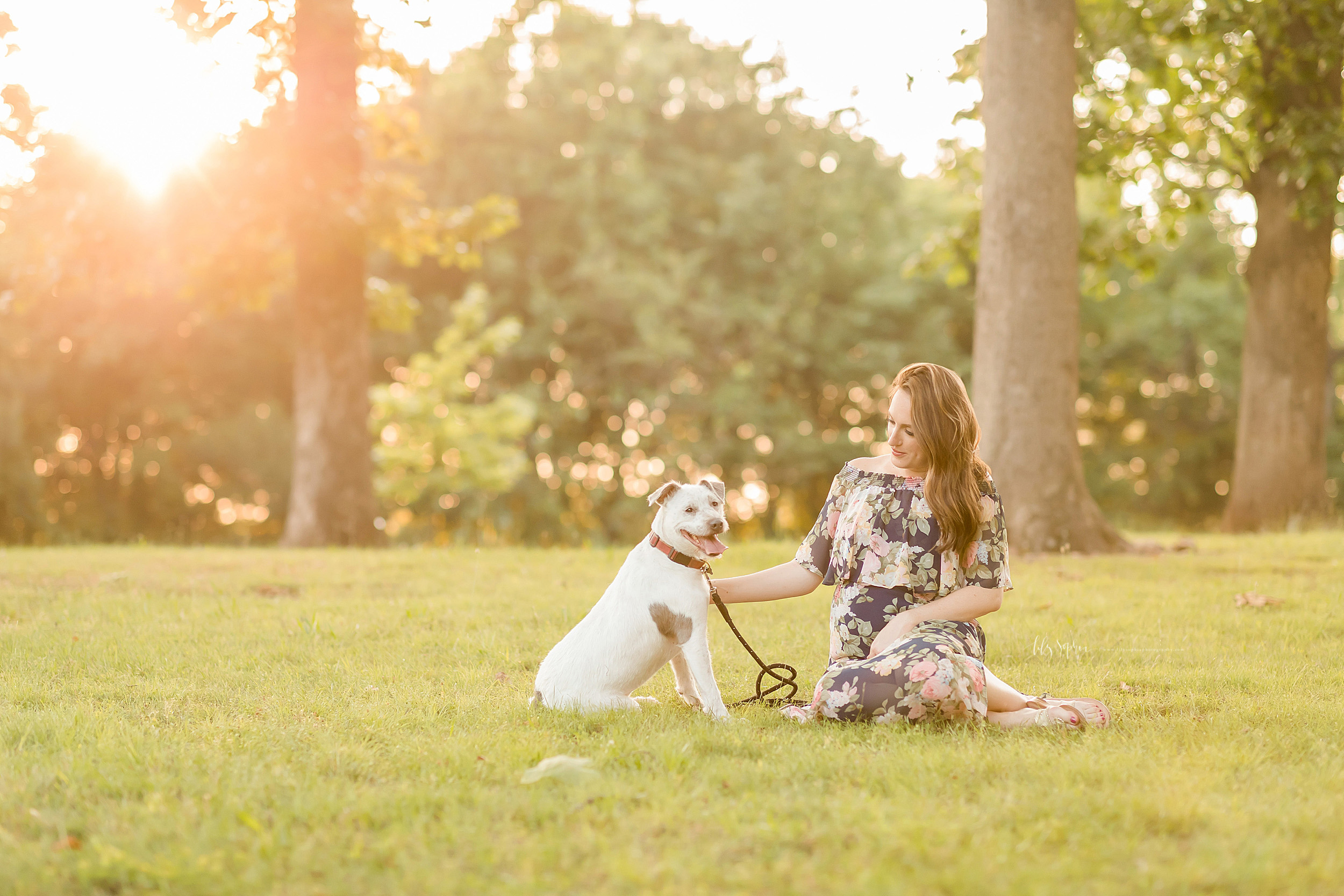 Maternity photo of a woman and her dog at sunset in an Atlanta park. The woman is sitting on the grass with her legs to her left. Her lab puppy is sitting to her left and facing her.  She has her right hand on her lap and her left hand is petting the side of the dog.  The dog's leash hangs to the ground from the dog's collar.  The sun streams in through the trees in the background.