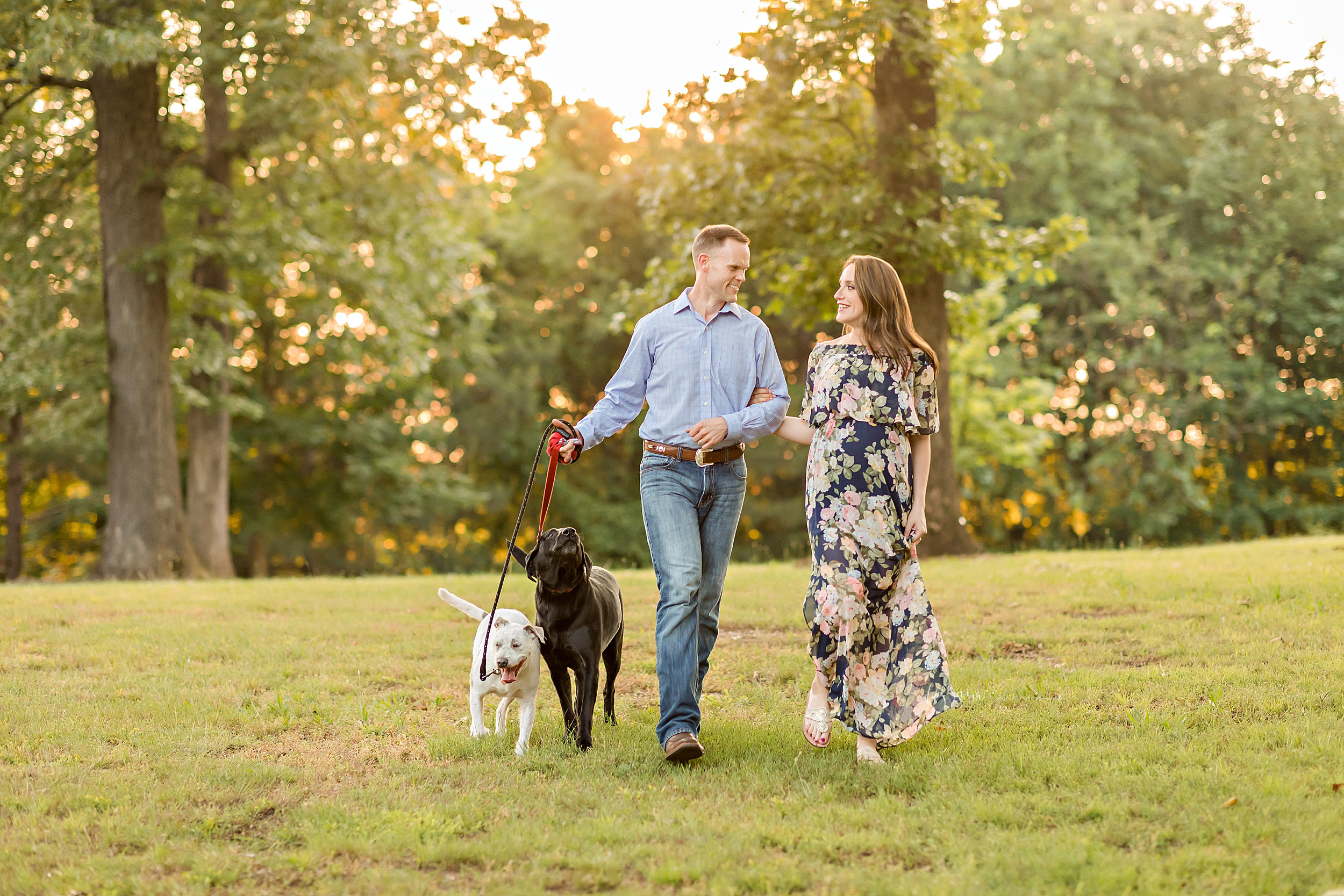 Maternity photo of an expectant husband and wife and their two dogs walking in a park in Atlanta.  The wife is holding the arm of her husband as she walks to the left of her husband.  The husband has the leashes of the black lab and the golden lab pups in his right arm.  The couple and their dogs are walking together in the park as the husband and wife turn their heads to look at one another.