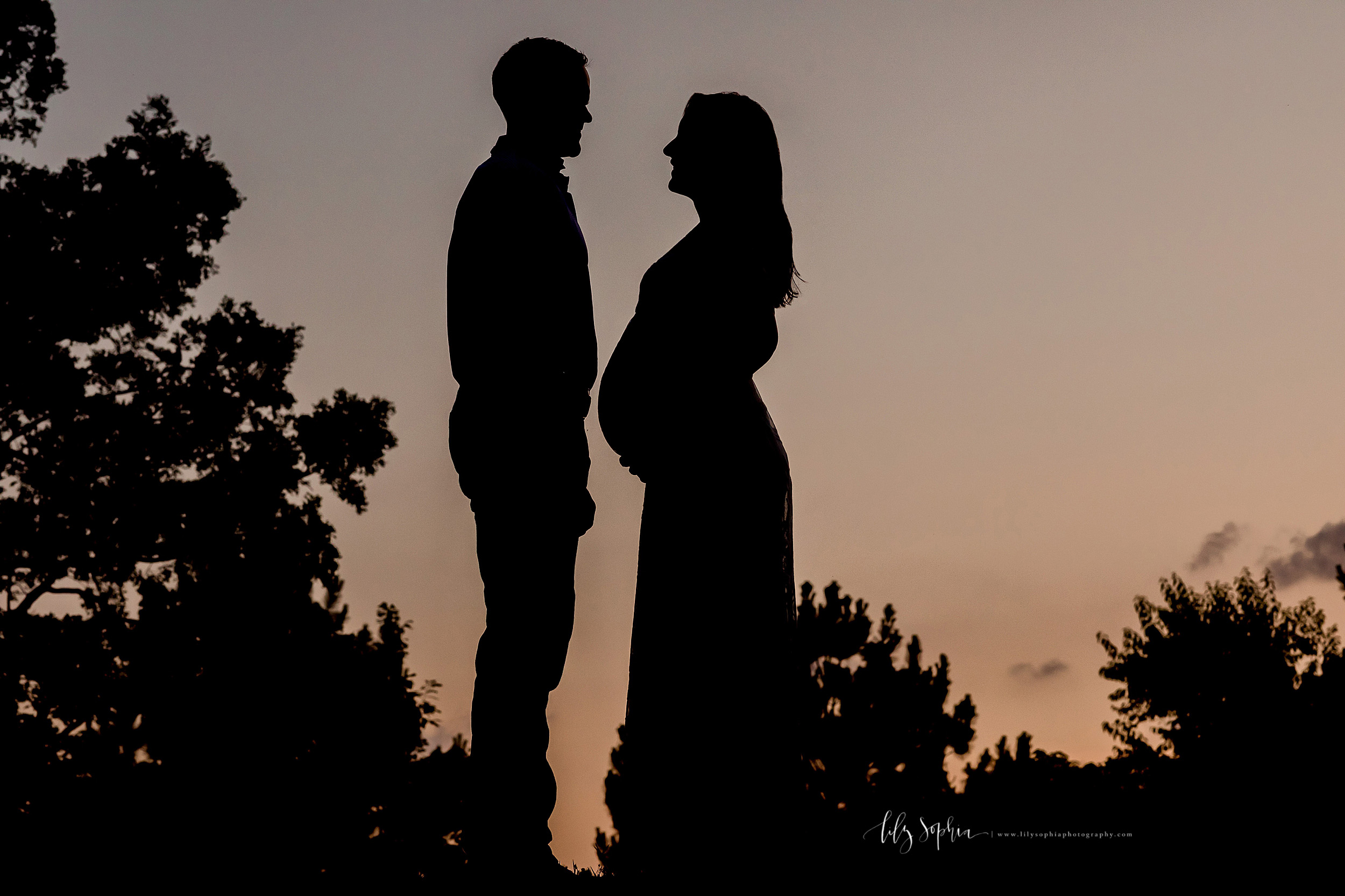 Silhouette maternity photo taken by Lily Sophia Photography at sunset in an Atlanta park.