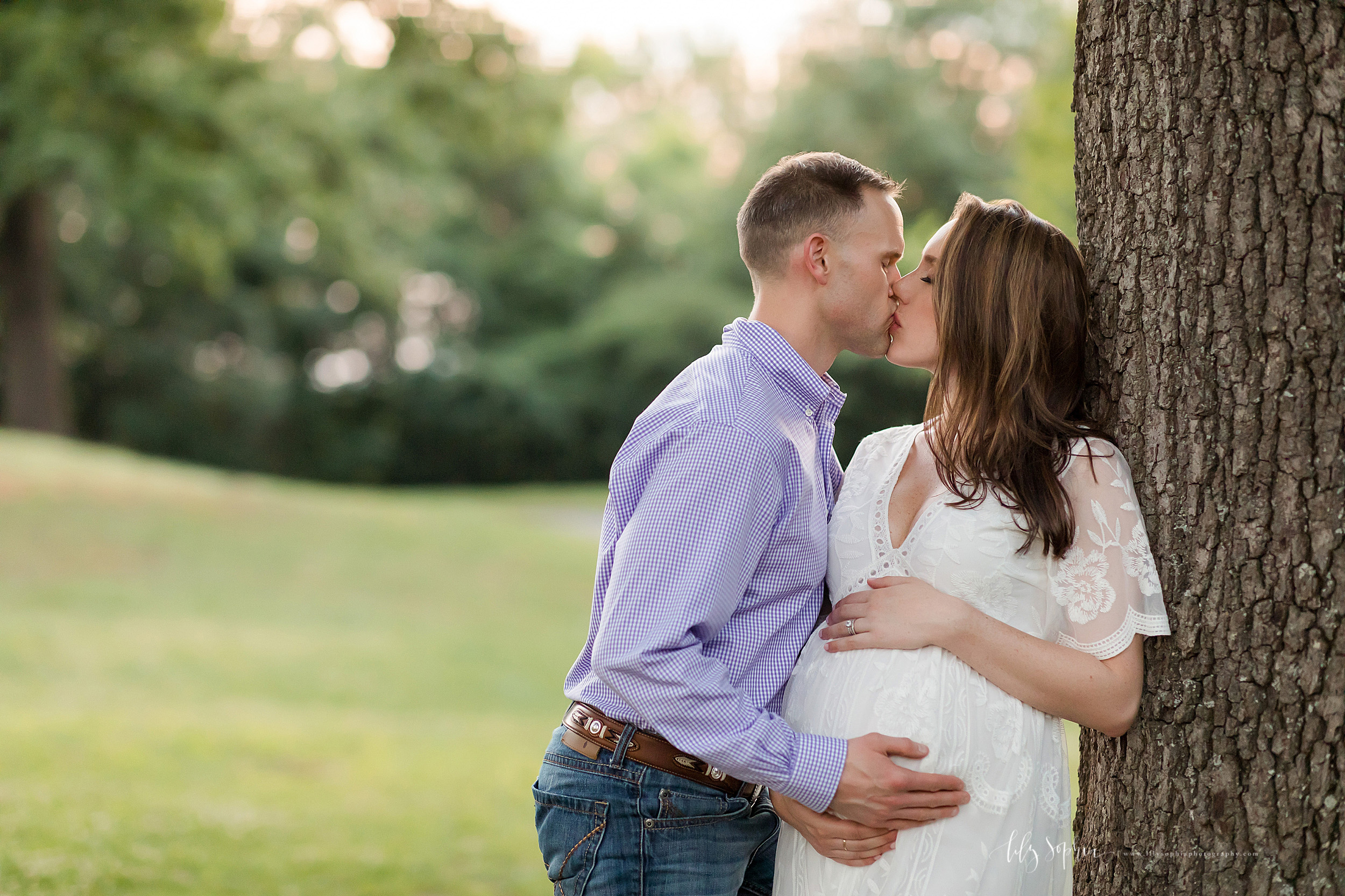 Maternity shoot of a couple in a park in Atlanta taken by Lily Sophia Photography. The wife has her back against a tree as the couple stand in the park. The husband is leaning into his wife as they place their right hands on her belly.  The wife has her left hand resting on the top of her belly.  The two are kissing one another.