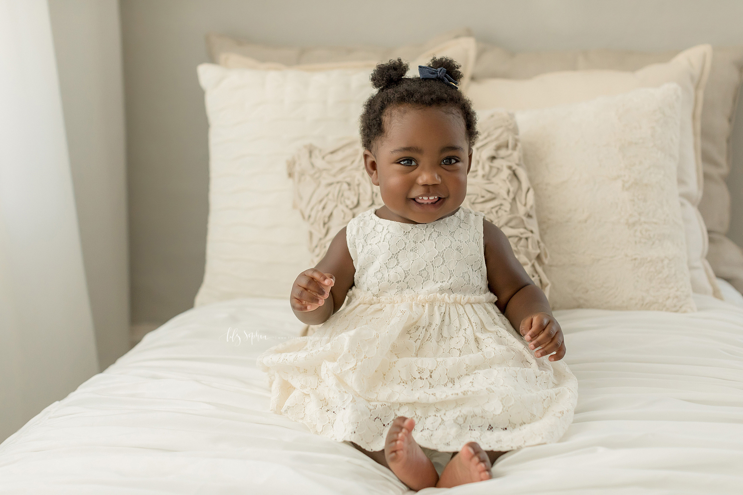 Image of a smiling African-American one year old girl for her first birthday taken by Lily Sophia Photography in a natural light studio in Atlanta.  The little girl is wearing an off-white sleeveless lace dress.  She has two ponytails on top of her head as she sits on a bed barefoot.