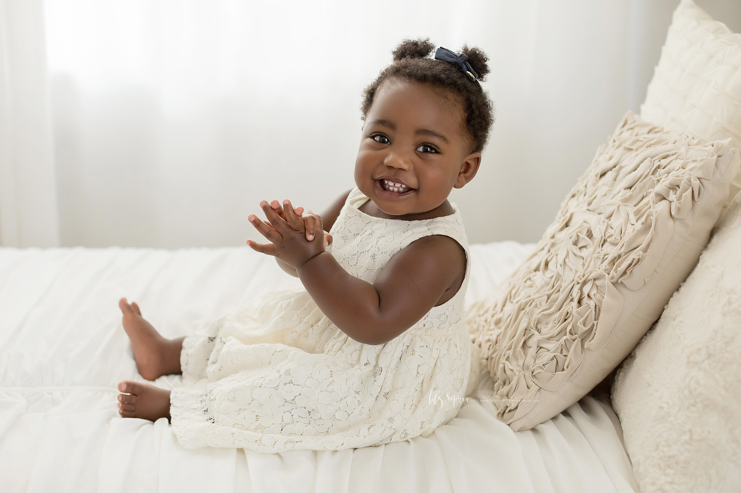 Photo of an African-American one-year old in a natural light Atlanta studio.  The little girl is sitting barefoot on a bed as she wears an off-white sleeveless lace dress.  She has two small ponytails on top of her head as she smiles and claps her hands.