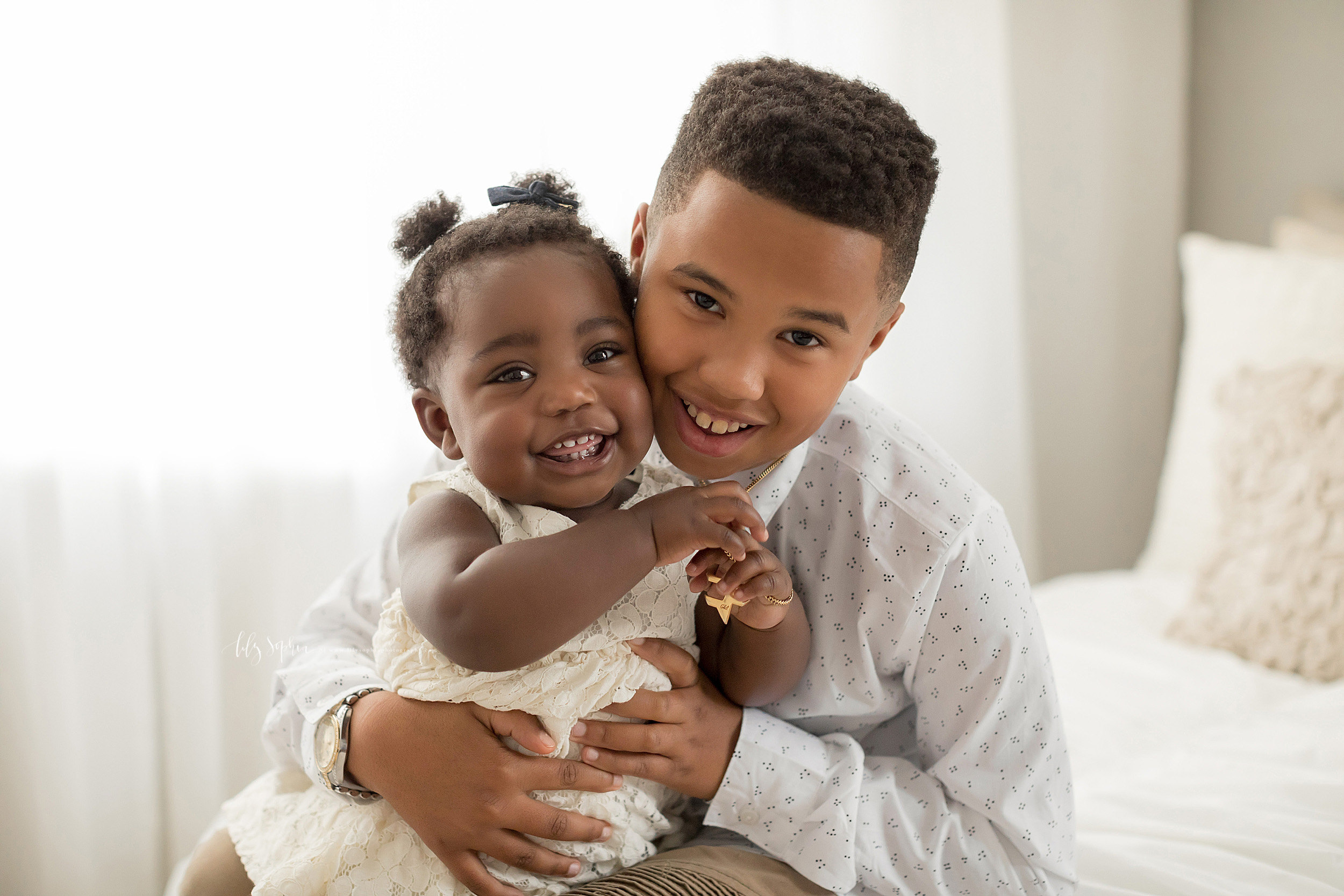Photo of a happy African-American brother and sister taken by Lily Sophia Photography in Atlanta.  The brother is holding his sister on his lap as the two are cheek to cheek while smiling.