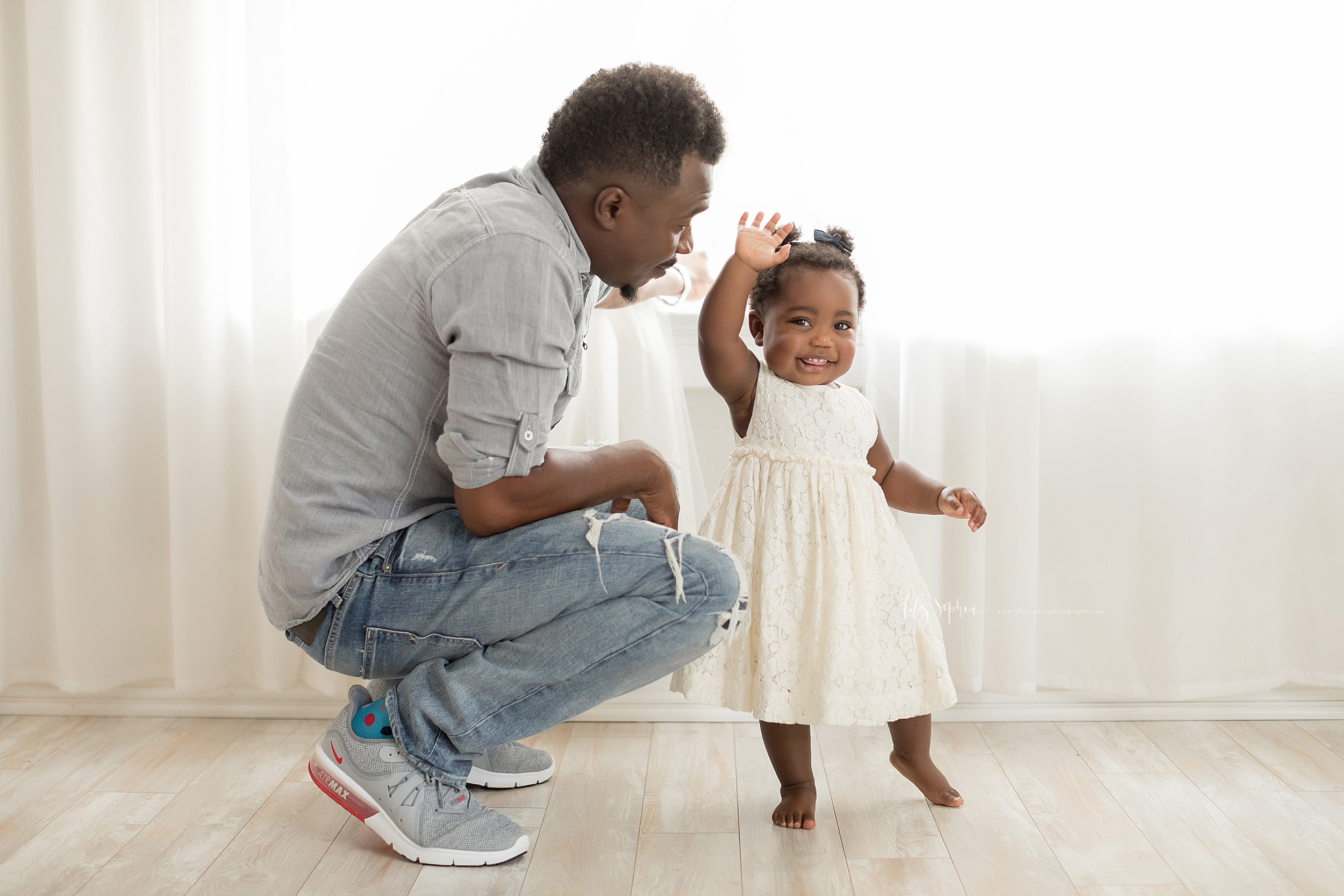Photo of an African-American dad and his daughter in an Atlanta natural light studio.  The father has a mustache and goatee squatting beside his daughter.  He is wearing a gray button down linen shirt with roll tab sleeves, wash ripped blue jeans and gray Nike sneakers.  His profile is shown as he faces to the right with his right hand resting on his right thigh.  His daughter is standing barefoot with her right hand in the air waving hello.  She is wearing an off-white sleeveless lace dress.