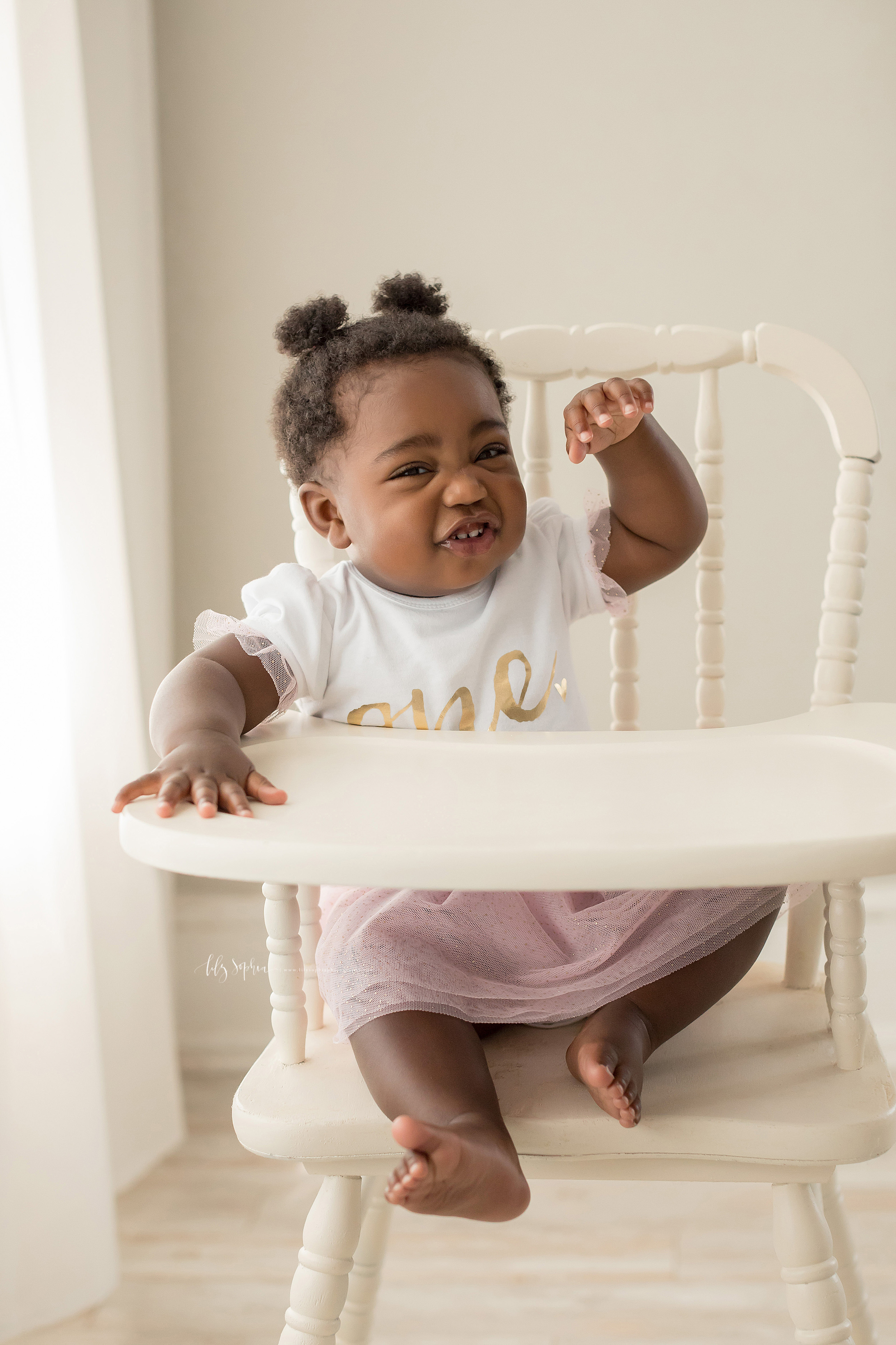 Milestone photo of a baby girl who is chattering and gesturing as she sits in an Atlanta studio in natural light in an antique high chair wanting her first birthday cake to be set before her.