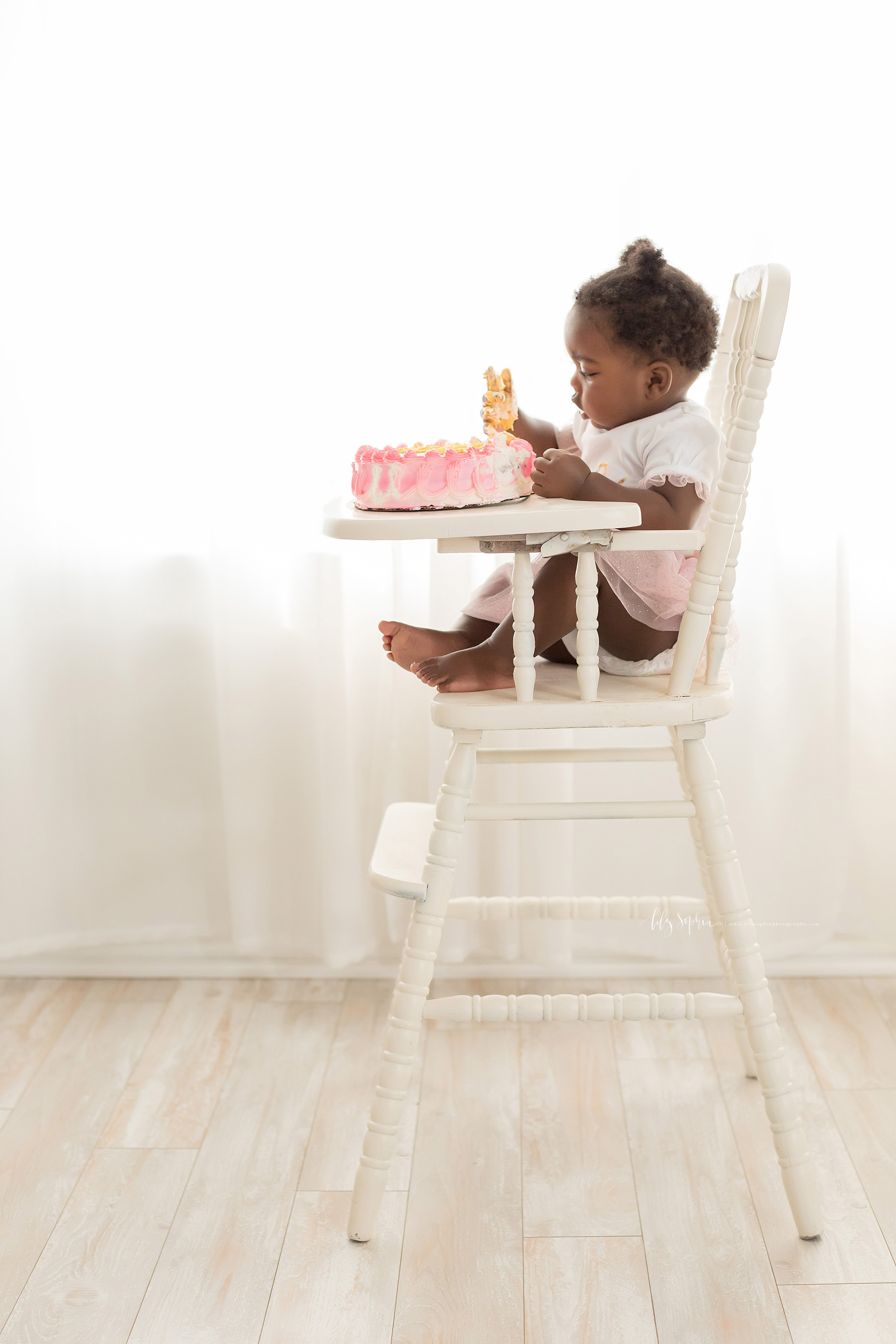 Photo of a cake smash by a one-year old African-American girl in an Atlanta natural light studio.  The little girl is sitting in an antique high chair with a pink, white, and yellow cake on the high chair tray.  She has put her right hand into the icing and is looking at her hand that is covered with yellow icing.
