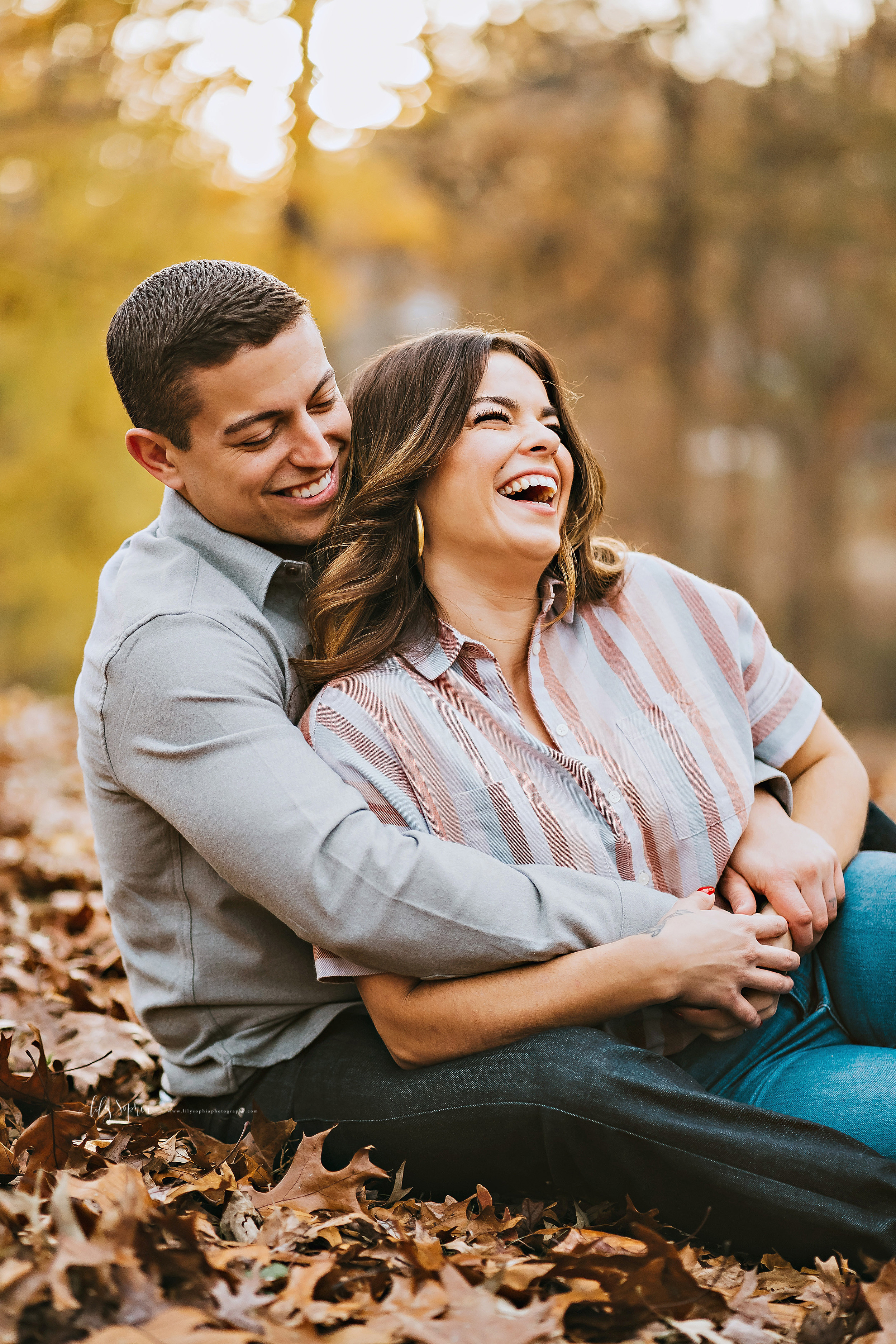 Photograph of a happy Atlanta couple during the fall in a park in natural light.  The woman is sitting between the man's legs with her back to his chest.  The man has his arms around her at her waist and she is holding his hands.  Both of them are laughing.