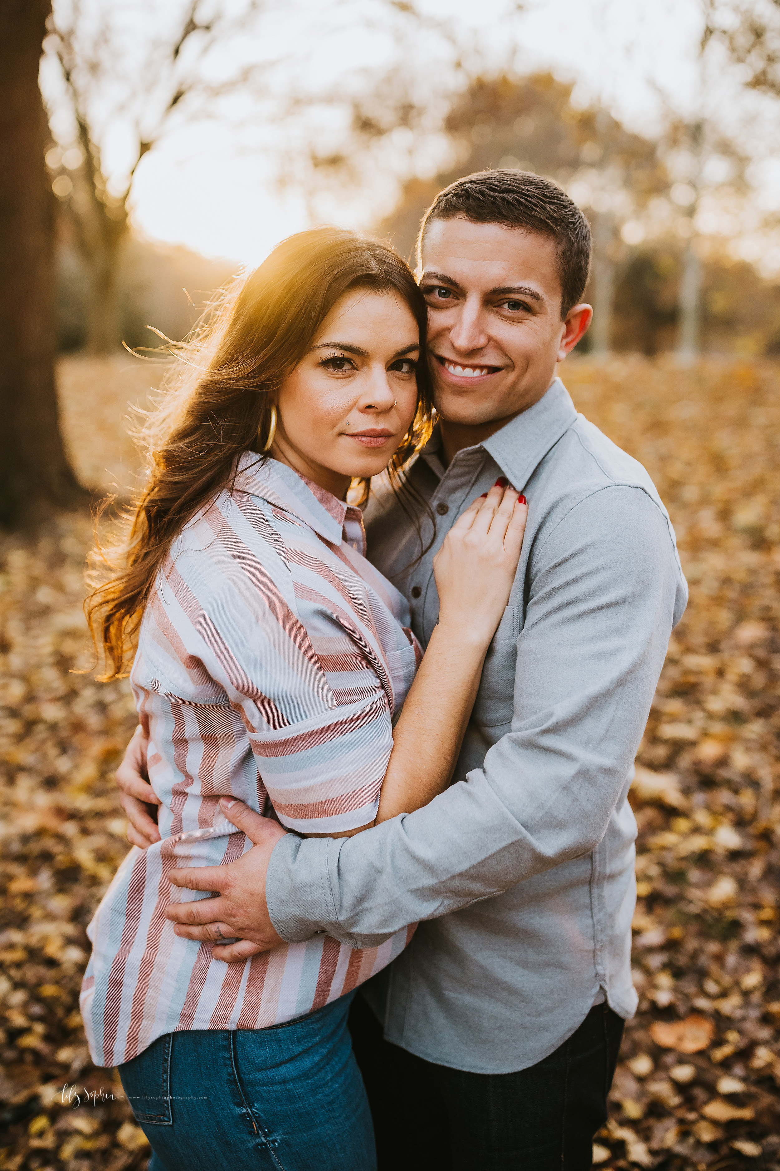 Photograph of an Atlanta couple in a park in Atlanta as the sun sets in autumn.  The woman and man are facing one another.  The woman has her right hand on the man's chest.  The man is smiling.