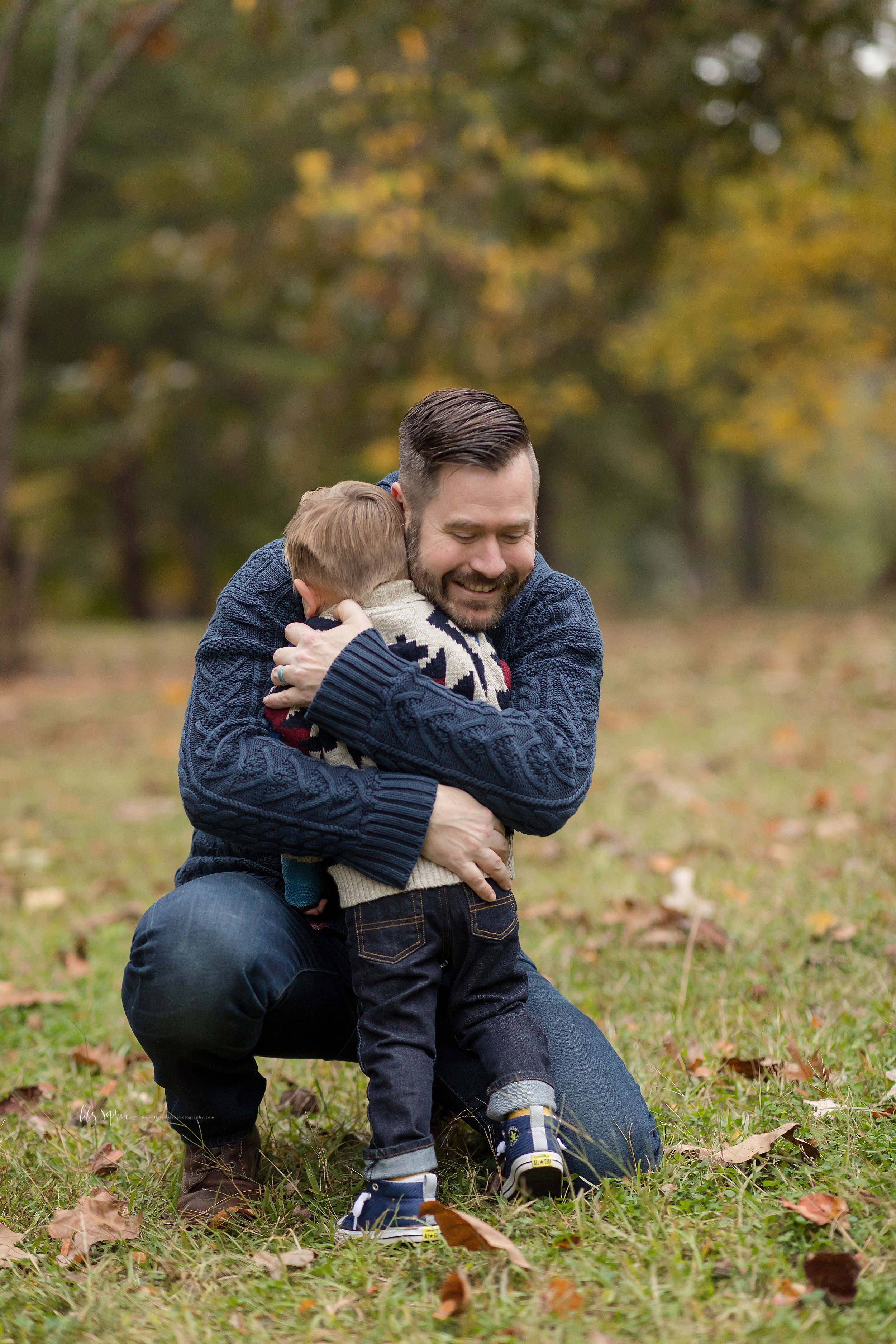 Photo of a young boy being embraced by his father as in a park during autumn in Atlanta.  The father is wrapping his arms around his young son as his son puts his face into his father's shoulder.