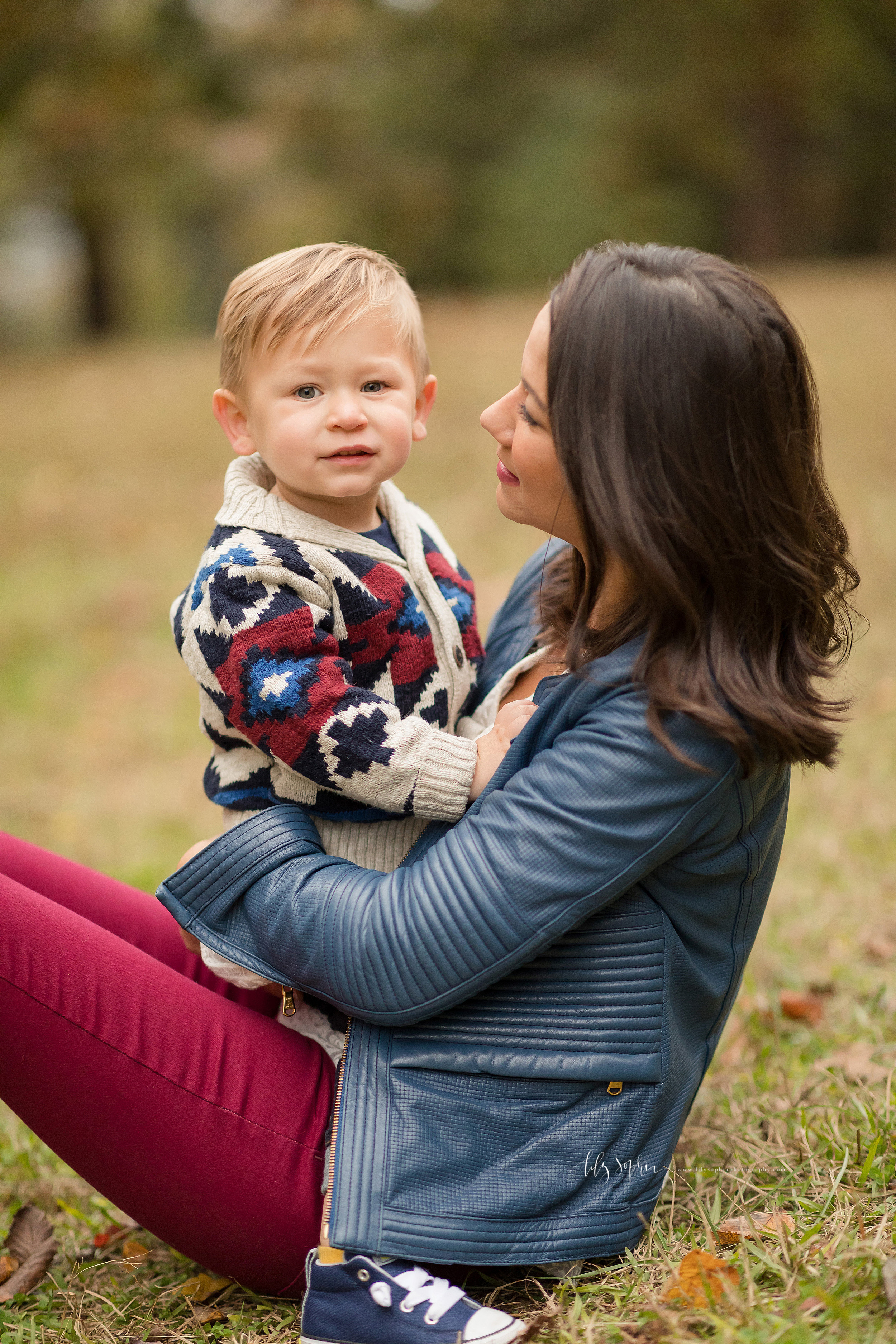 Photo of mom and her son in a park in Atlanta taken by Lily Sophia Photography in autumn. The blond haired son is straddling his brunette mom who is sitting on the grass with her legs bent.