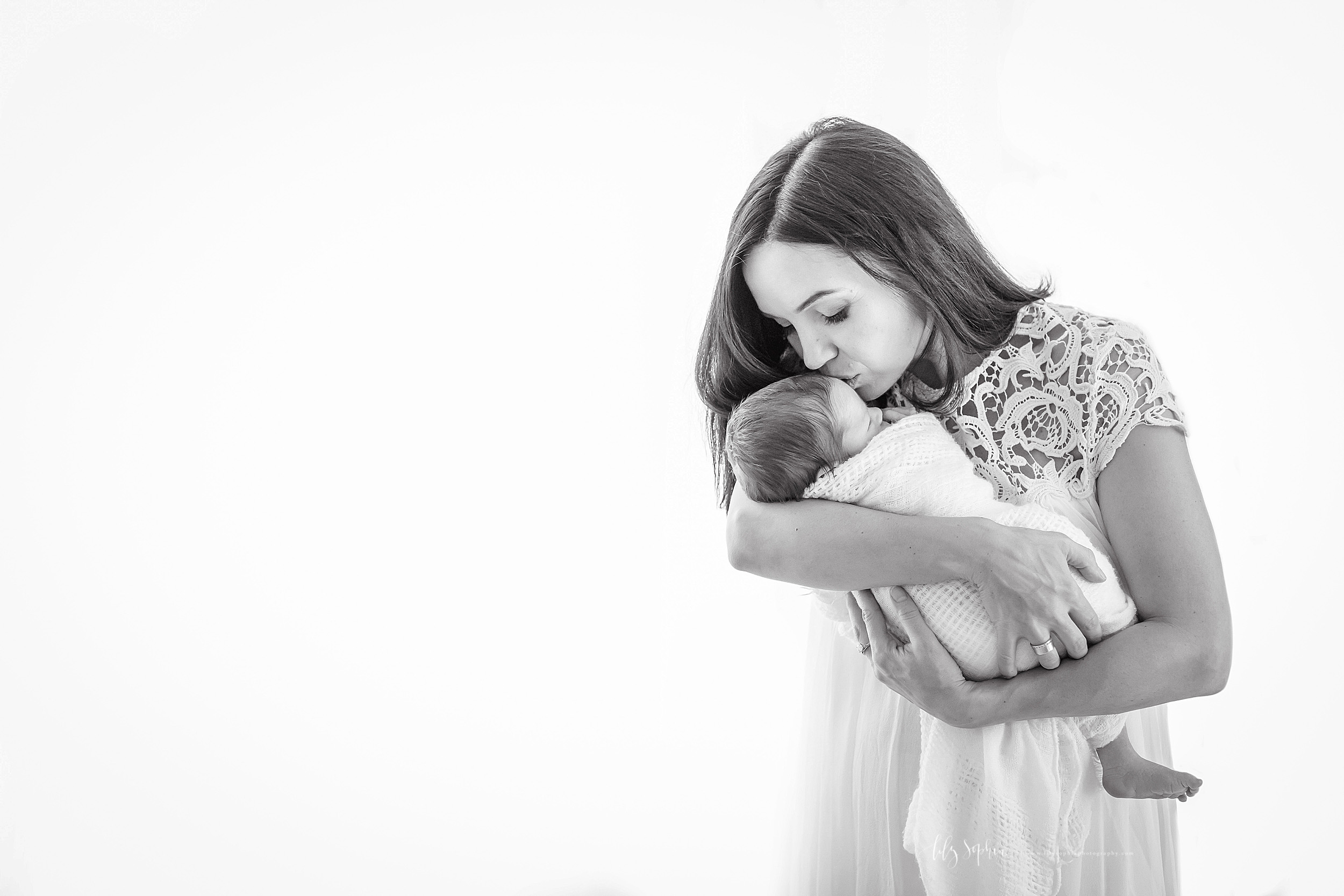 Photo of a mother and her newborn in a natural light studio in Atlanta. The brunette mother is holder her newborn son in her arms as she is standing. The newborn is asleep swaddled in a blanket with just his right foot and his head showing.  Mom has her eyes closed and is kissing the forehead of her son.