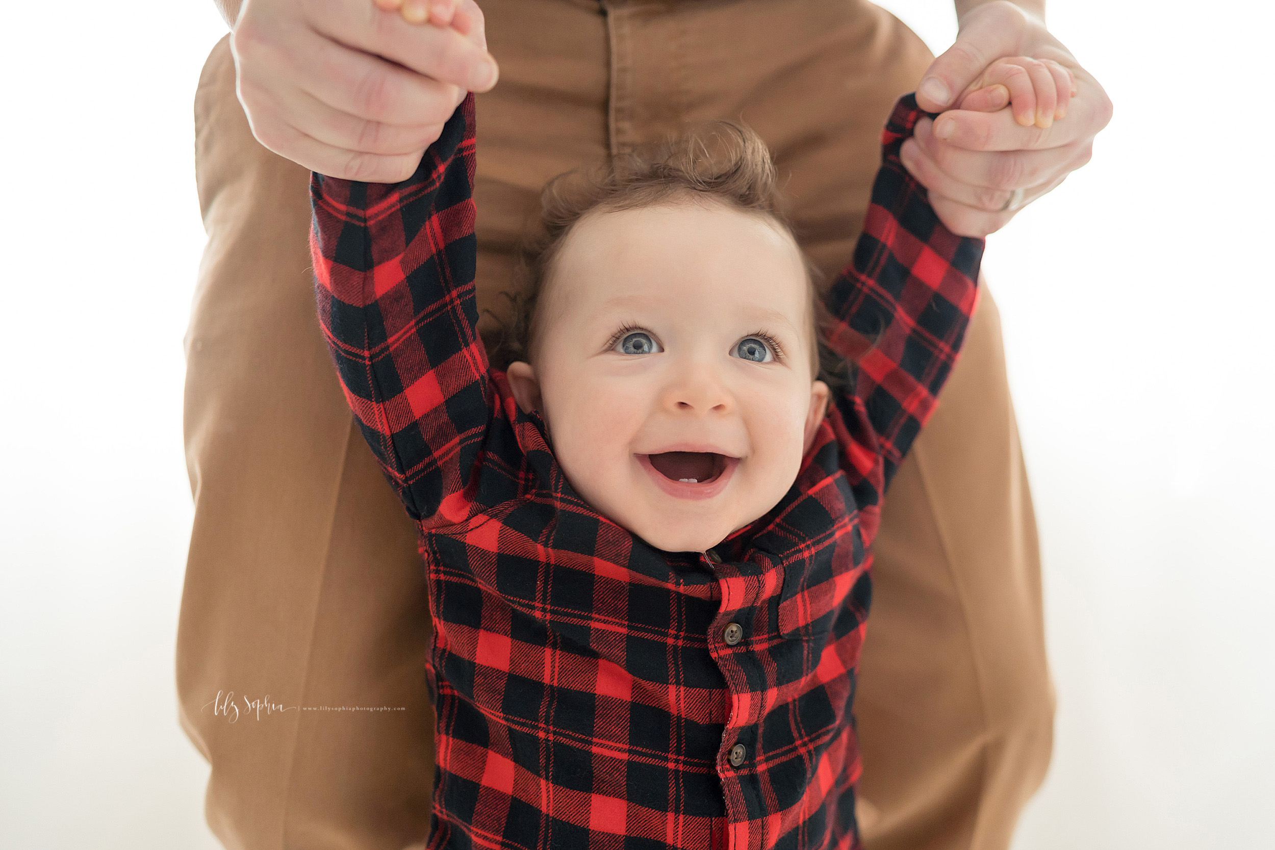 First birthday photo of a one year old as he walks in front of his father.  The curly haired, blue eyed little boy with eyes wide and bright holds his fathers hands to help him walk.  The boy has a smile on his face and you can see his two front teeth on the bottom.