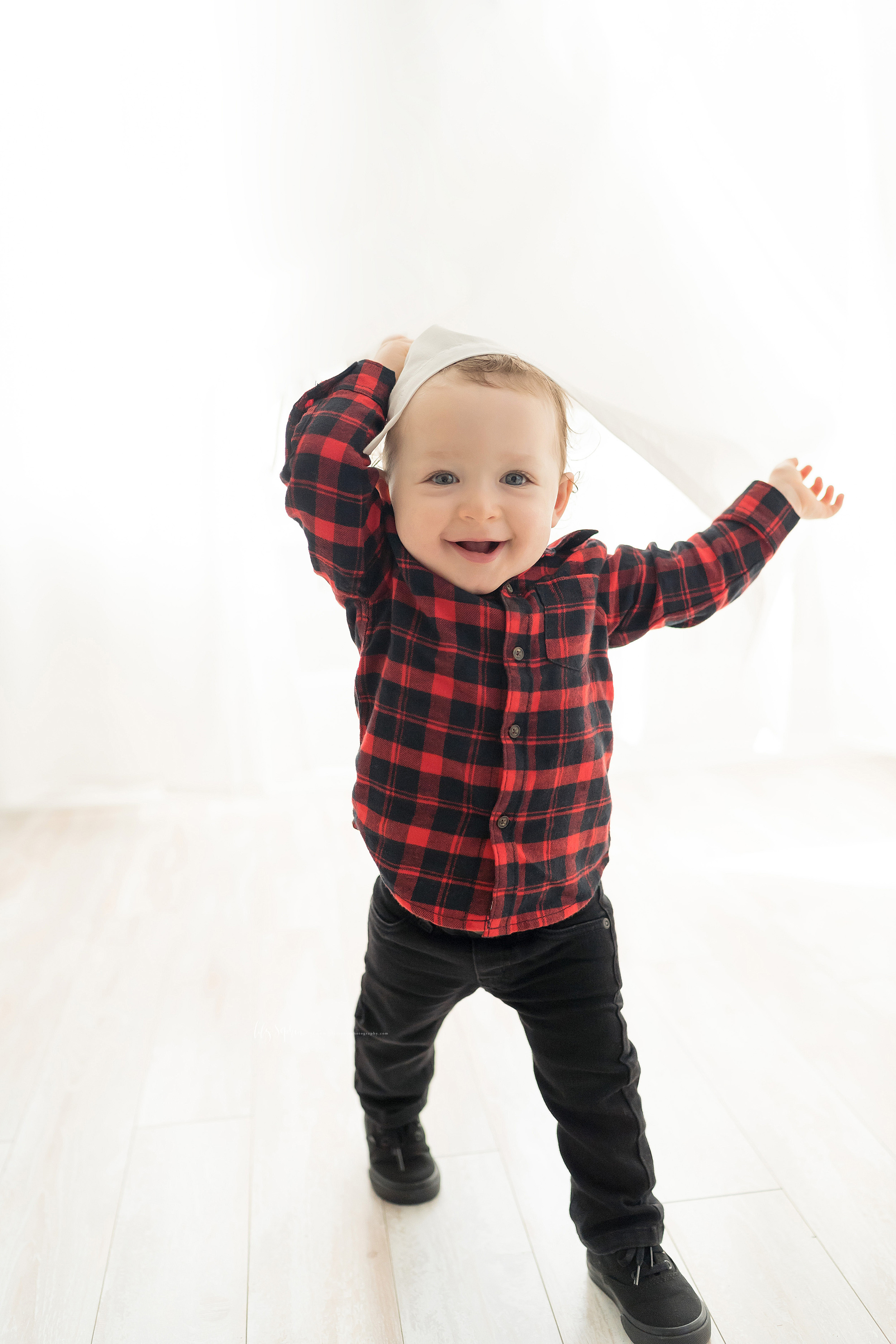 Photo of a one-year old little boy as he plays peek-a-boo from behind the curtains in an Atlanta natural light studio.