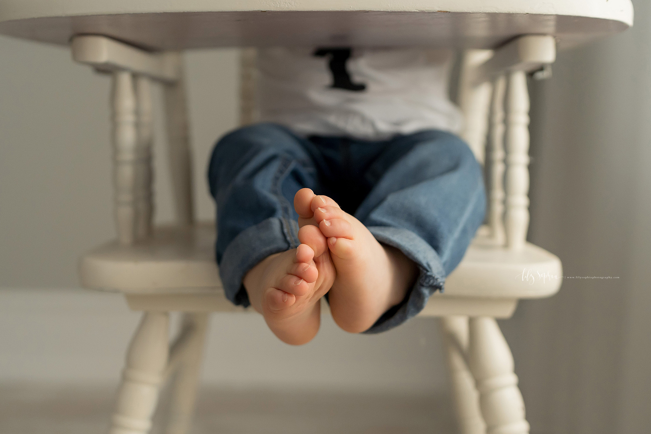 Milestone image of a one-year old as he sits in an antique high chair.  The photo shows his sweet legs and feet.