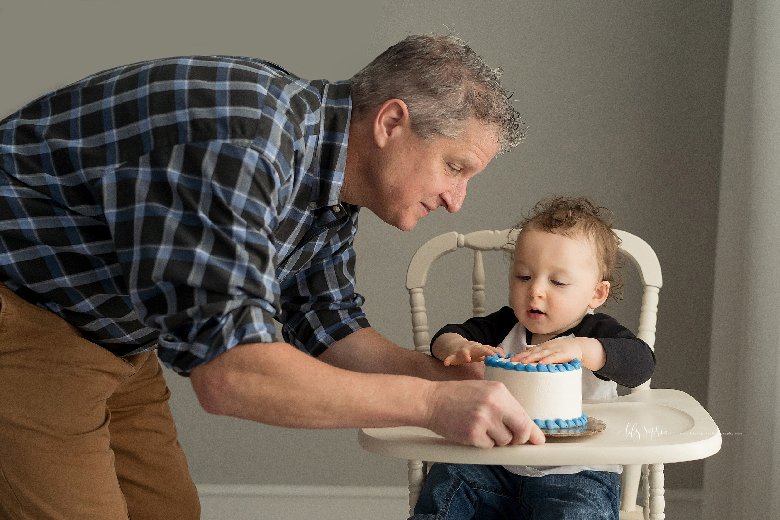 Photo of a father and son on his son's first birthday. The father is putting a cake in front of his son as his son sits in an antique high chair, pats the cake with his hand, and looks on with anticipation.