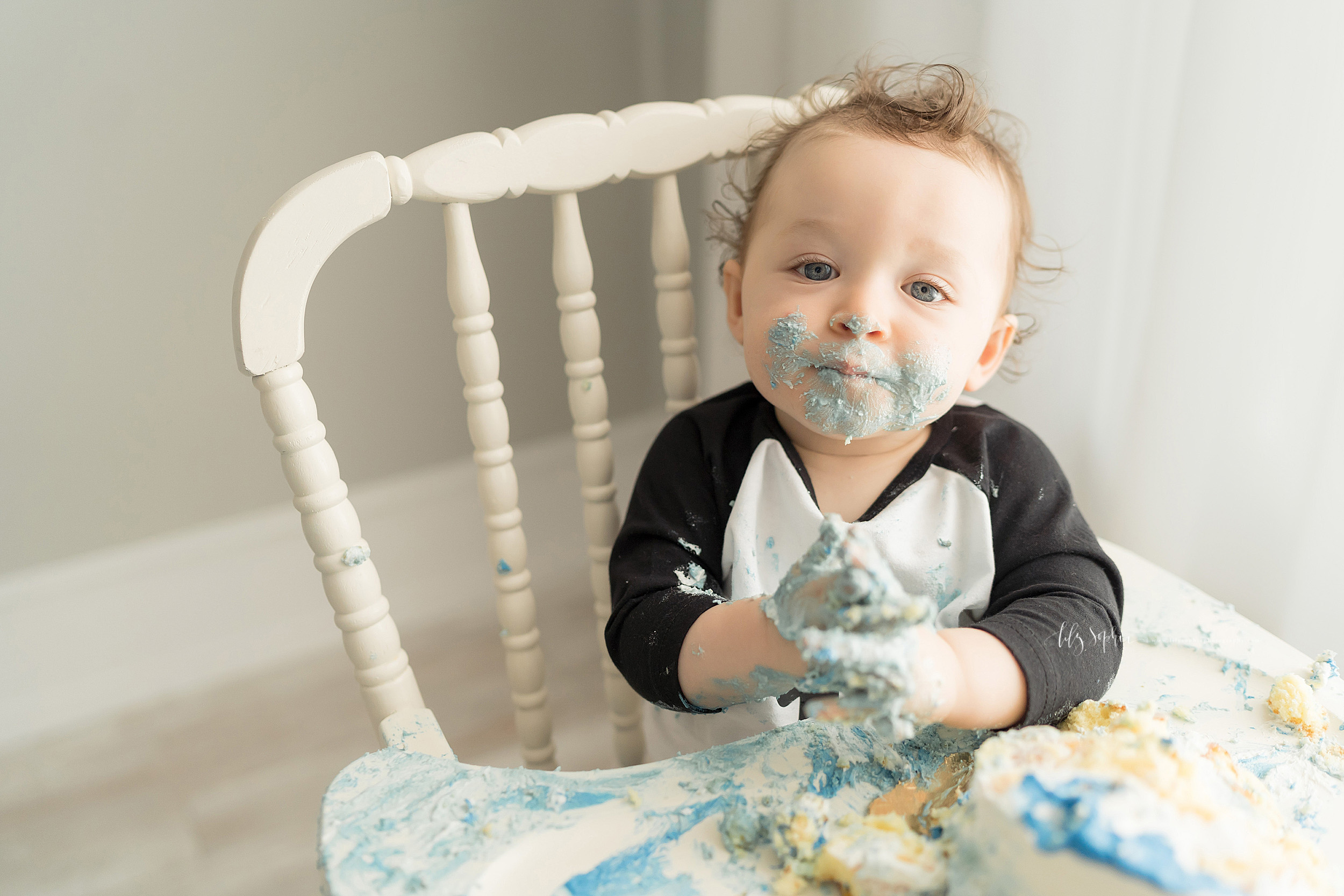 Cake smash photo of a one year old boy taken in a natural light Atlanta studio.  The happy curly haired little boy is sitting in an antique high chair with blue icing on his face and hands and cake and icing smashed all over the high chair tray.