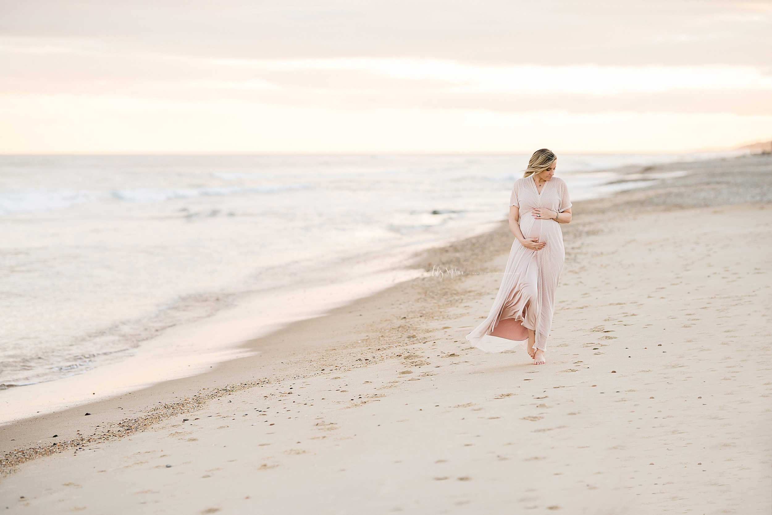 Maternity photo of a woman as she walks at sunset along a beach in Long Island, NY taken by Lily Sophia Photography.