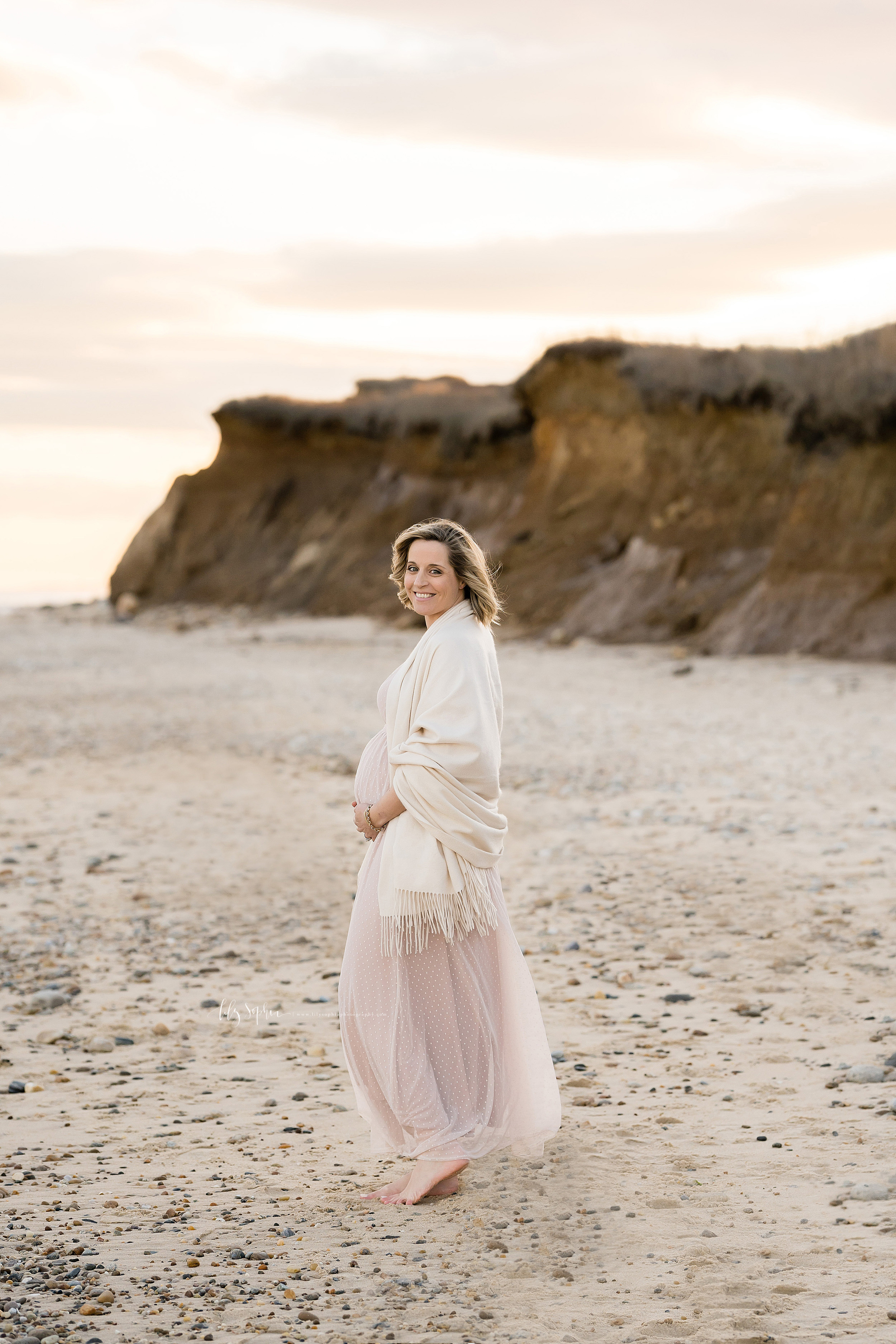 Photo of a happy pregnant woman standing on the beach beside the cliffs of Montauk taken by Lily Sophia Photography at sunset in April.