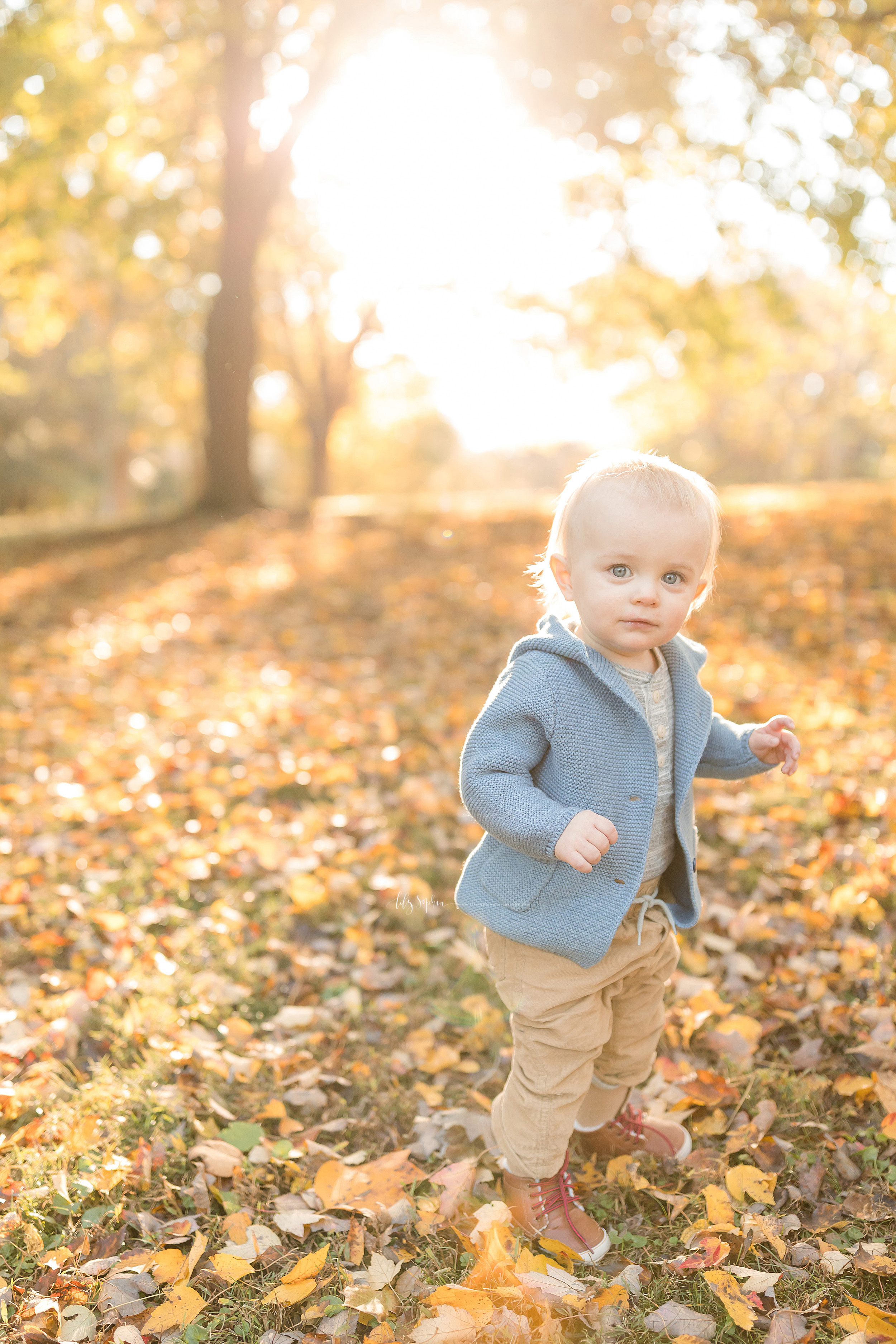 Milestone photo of a blonde haired, blue eyed baby boy during the fall at sunset walking in the leaves in an Atlanta park.