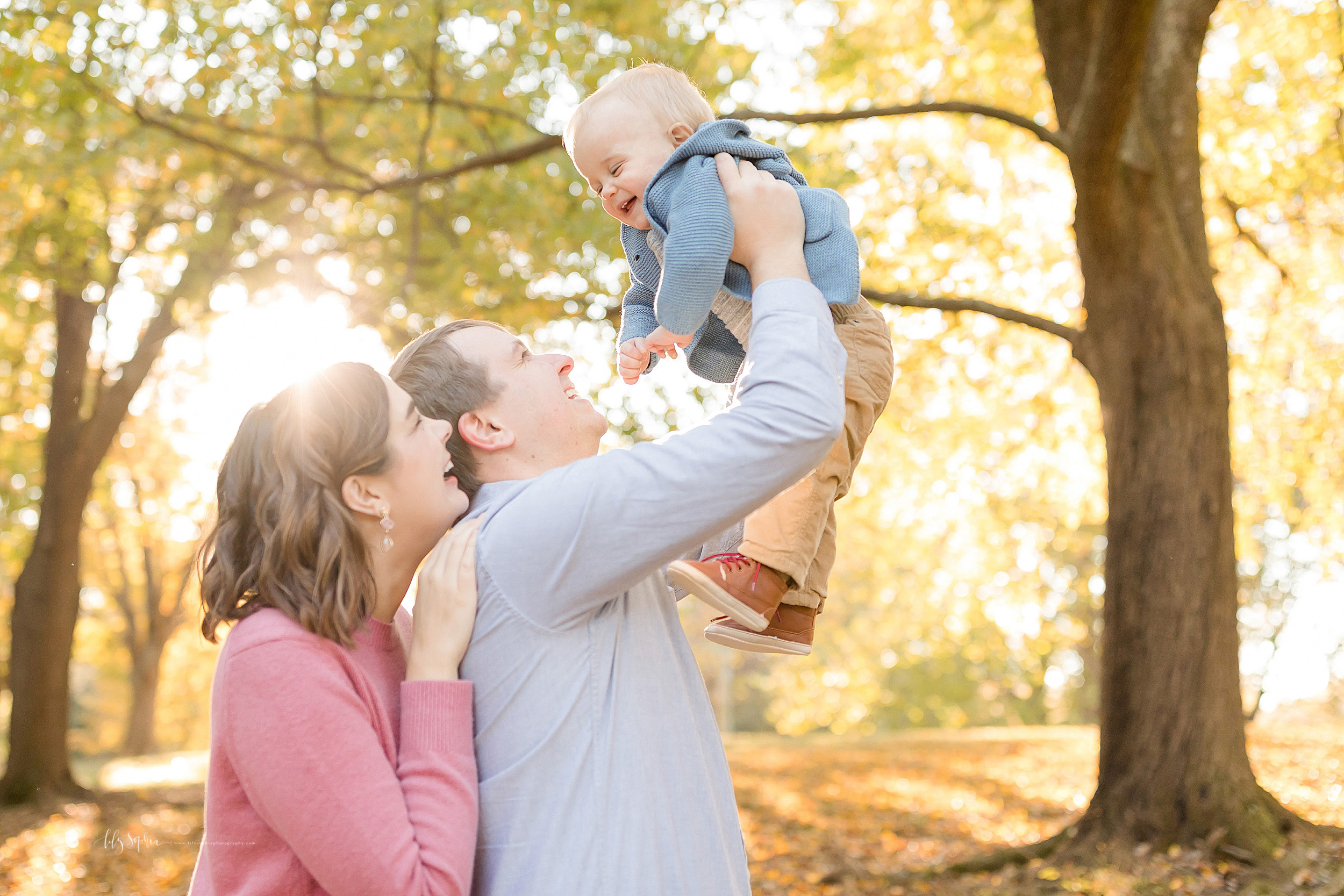 Family photo of a happy family of three in a park as they play in Atlanta in autumn at sunset.  Mom is standing behind dad and has her right arm on dad's right shoulder.  Dad is lifting his one year old son up above his head as the baby boy giggles and the parents smile.