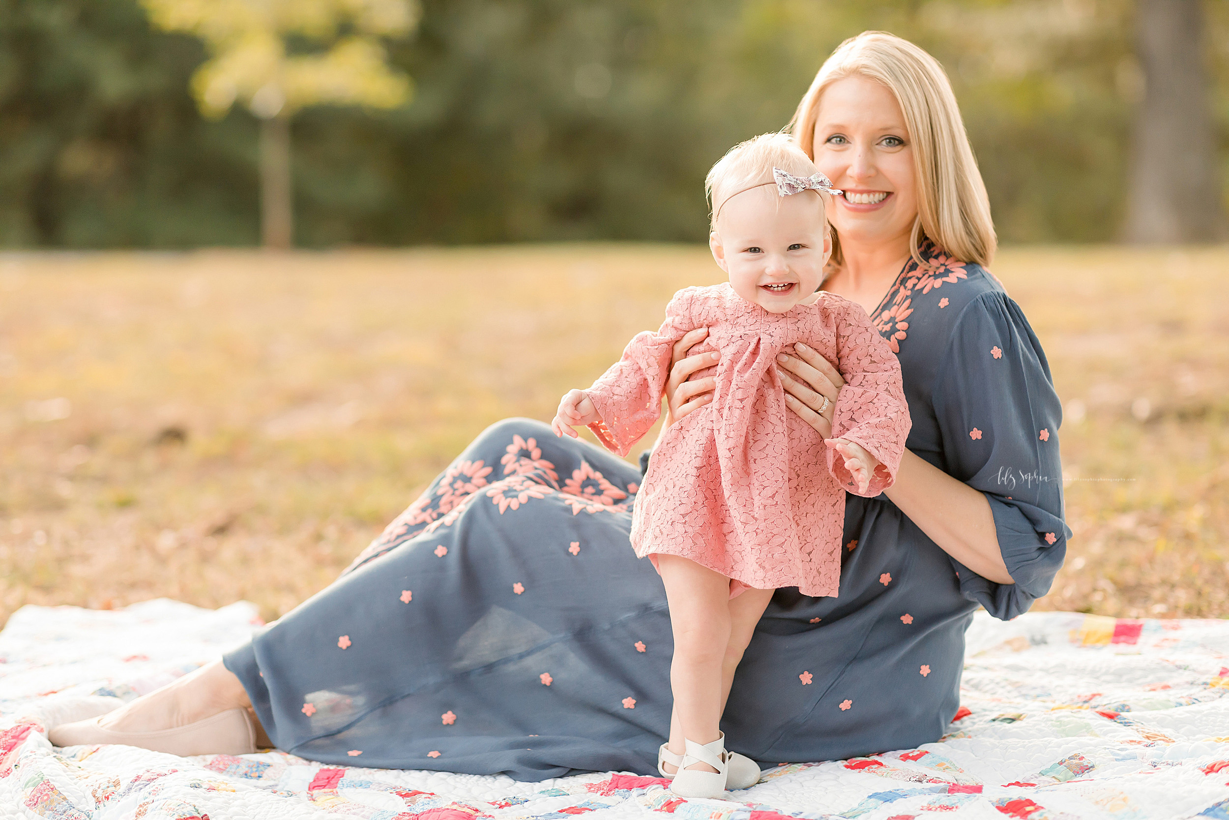 Family photo of mom and her daughter as mom sits on a quilt and her daughter stands next to her with her mom's help in Atlanta at a park at sunset.
