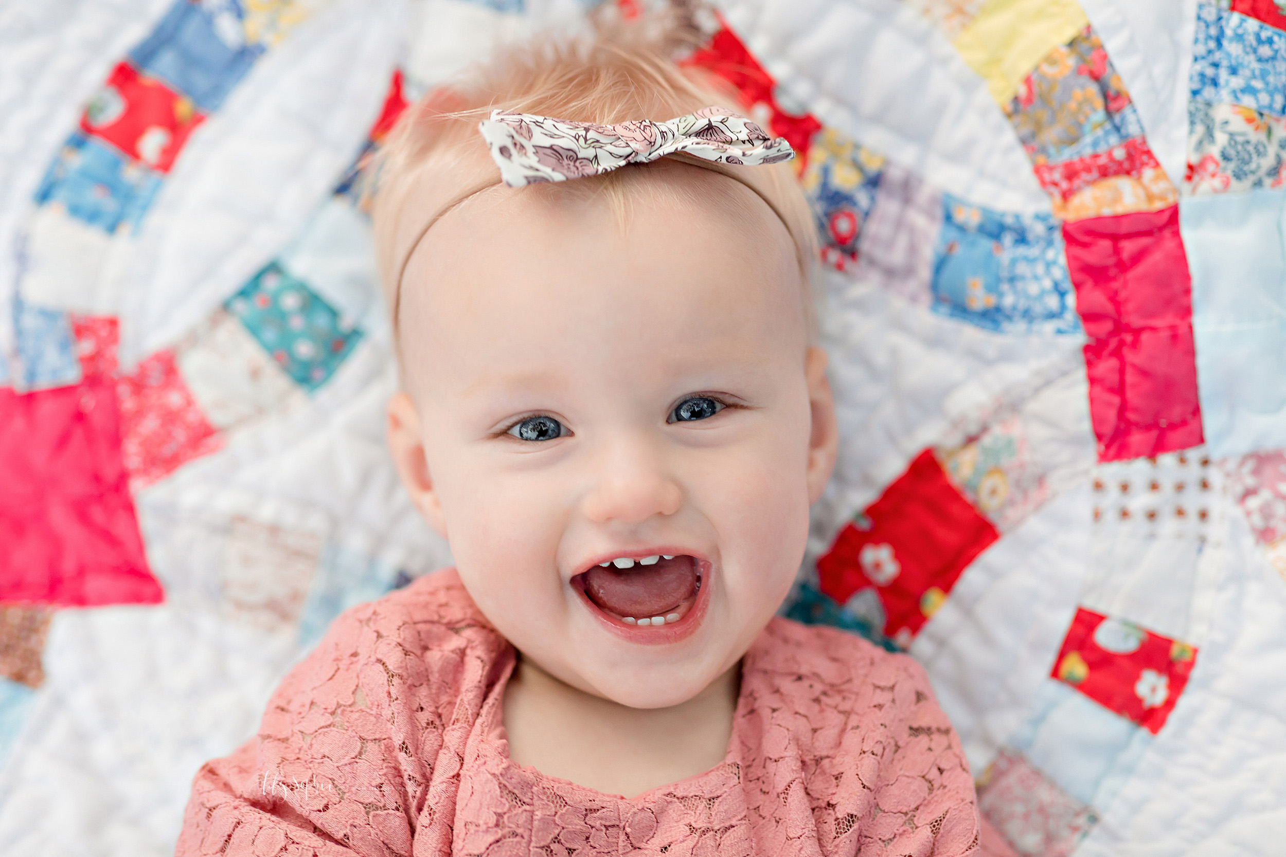 Milestone photo of a smiling one year old little girl laying on a quilt wearing a pink lace dress and a floral bow head band taken by Lily Sophia Photography.