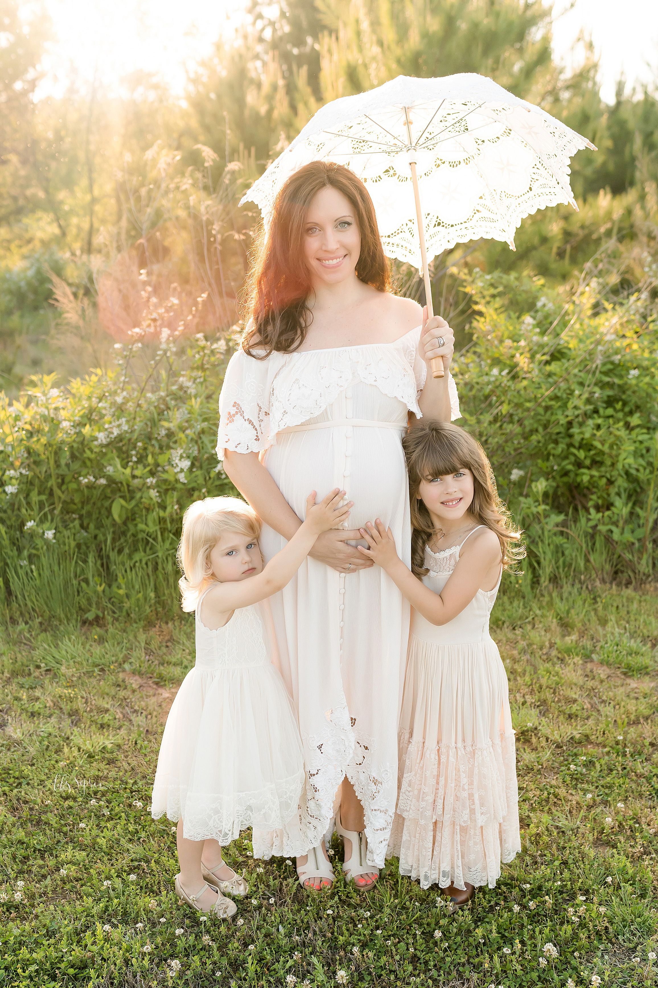 Family photo of a pregnant mother and her two children as they embrace the baby in utero while standing at sunset in a field in Atlanta.
