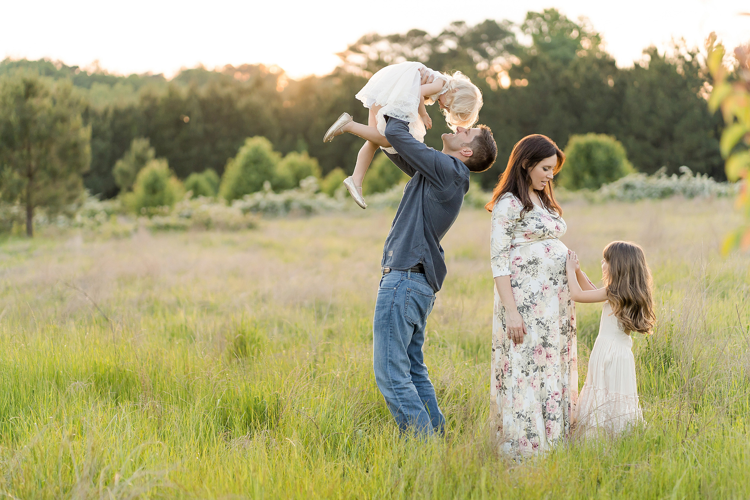 Family photo of four playing in an Atlanta field at sunset.  Dad is lifting his blonde haired daughter above his head while his brunette daughter touches her mother's pregnant belly.