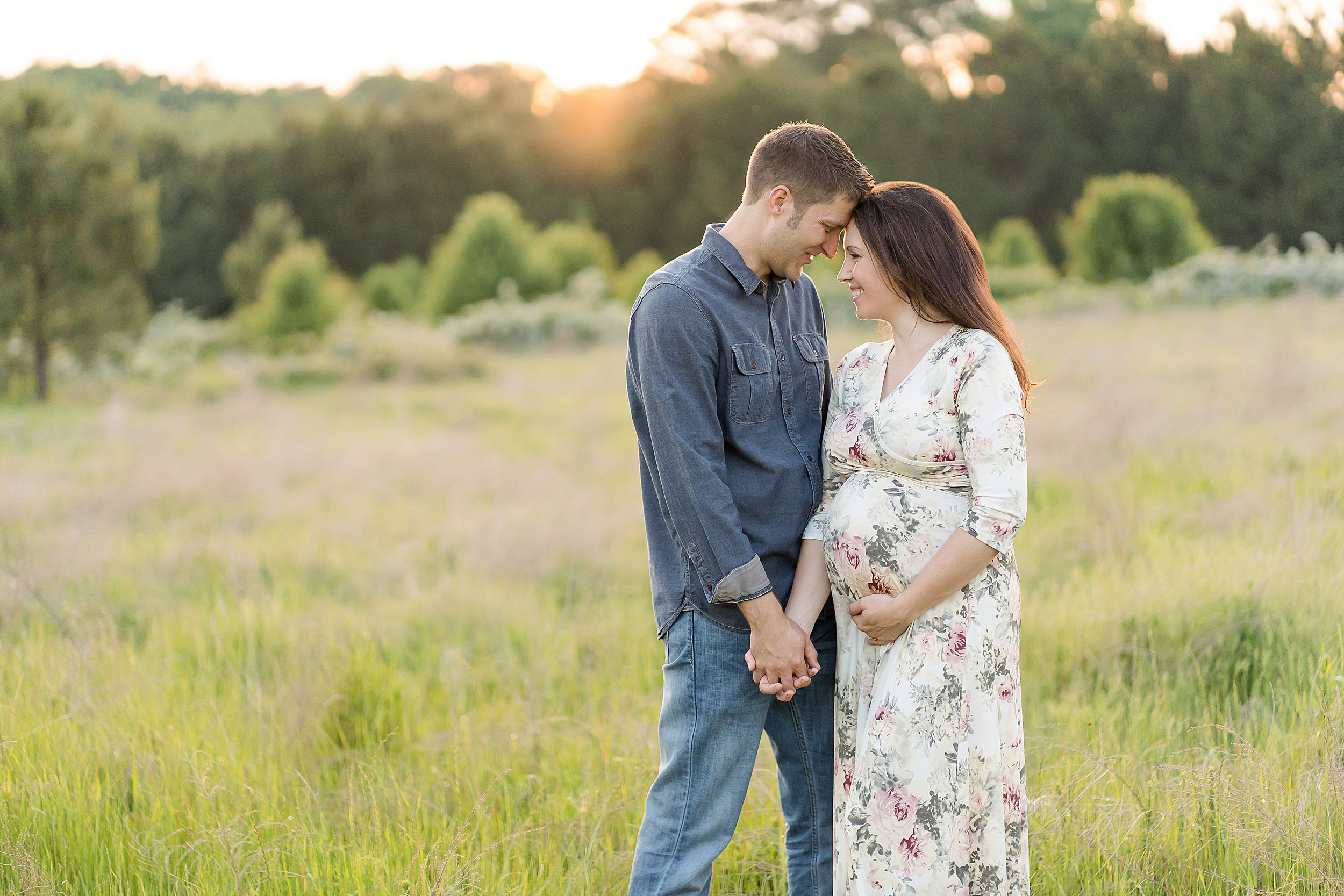Maternity photo of a husband and wife at sunset holding hands and putting their foreheads together at sunset in field in Atlanta.