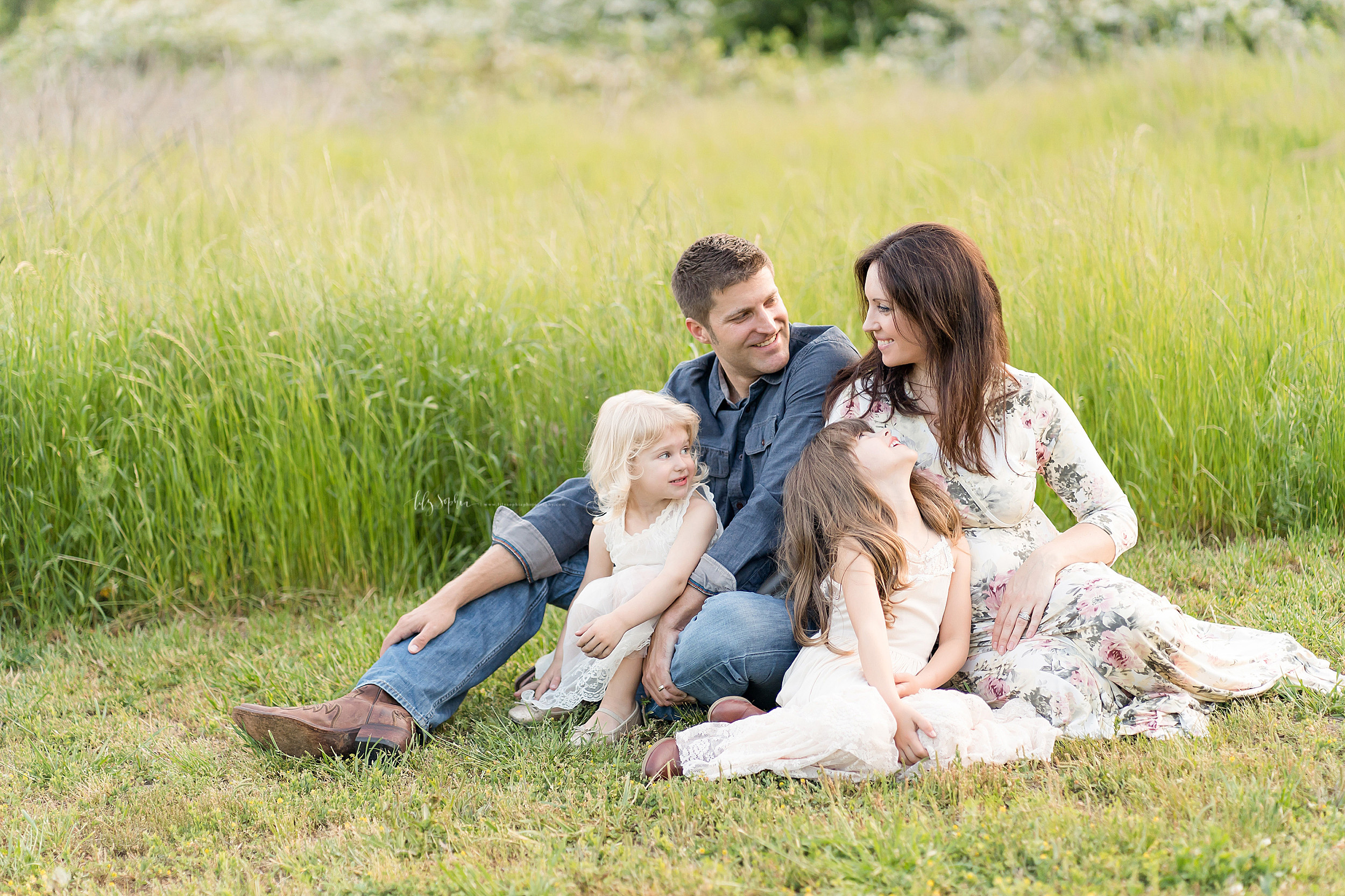 Photo of a family of four sitting in a field in Atlanta at sunset enjoying each other's company.