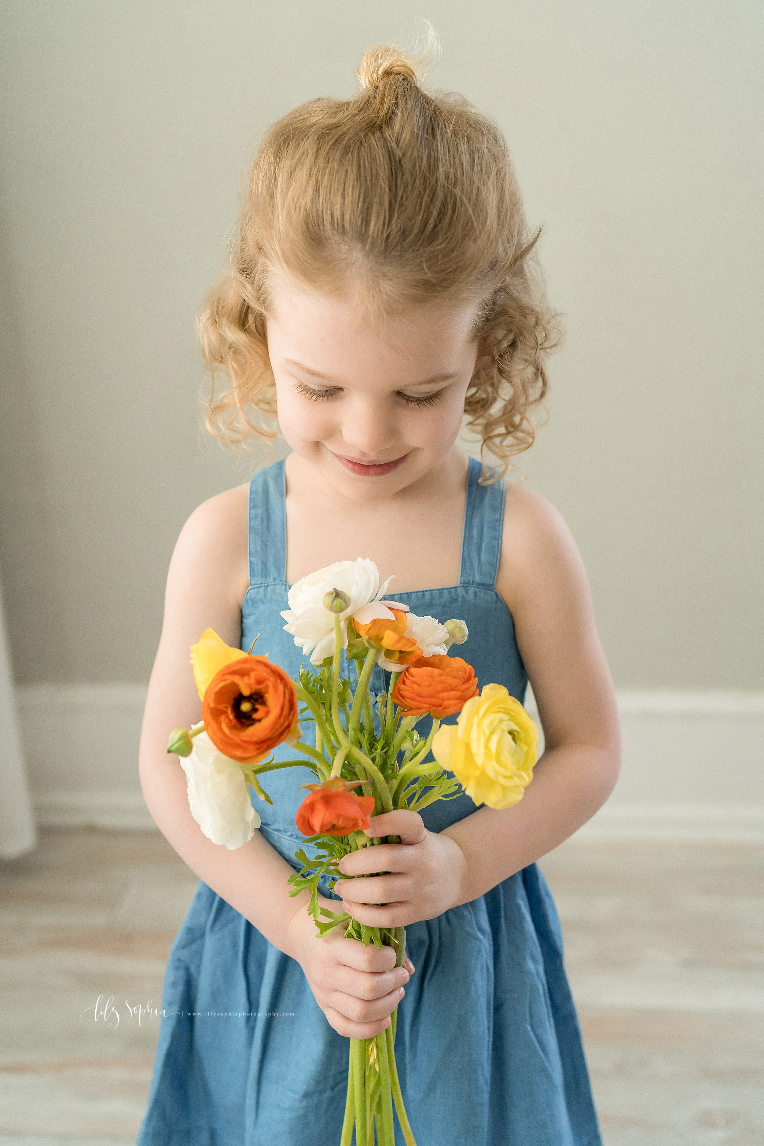 Milestone photo of a four year old little girl holding a bouquet of flowers and wearing a denim sleeveless jumper in a natural light studio in Atlanta.